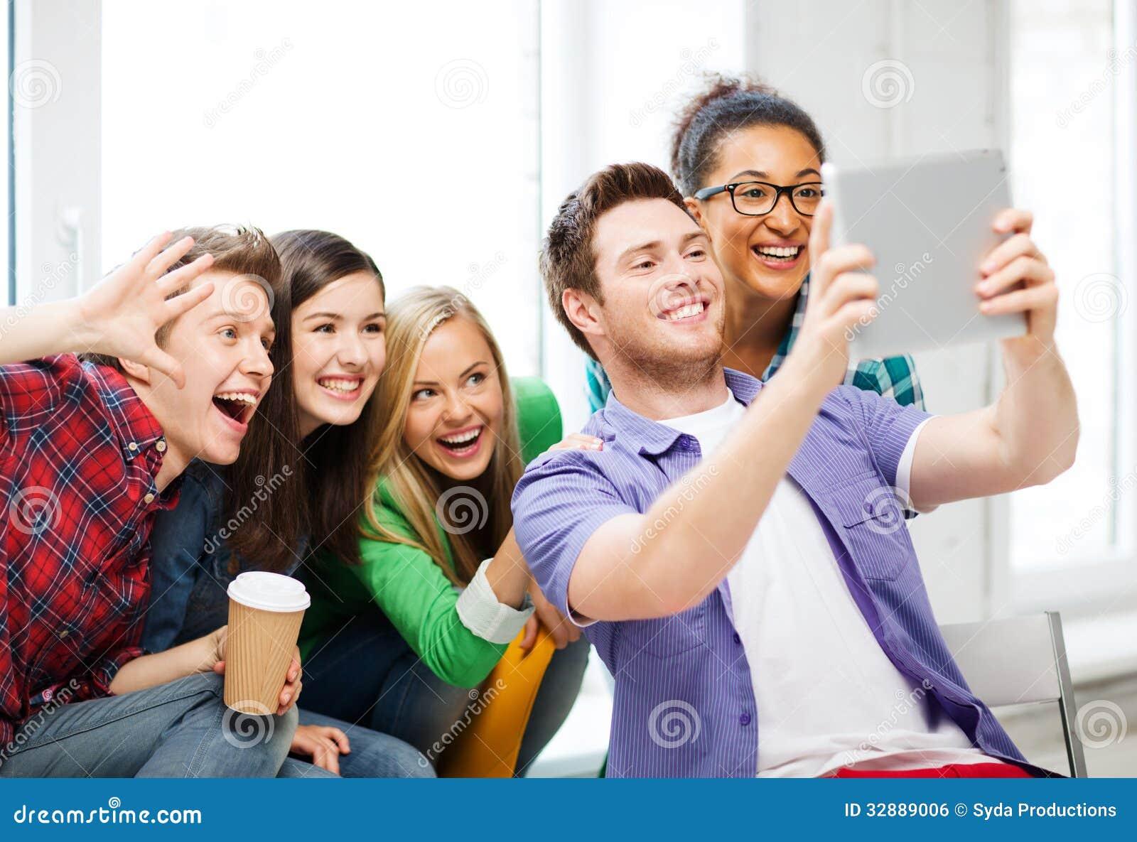 Estudantes que fazem a imagem com o PC da tabuleta na escola
