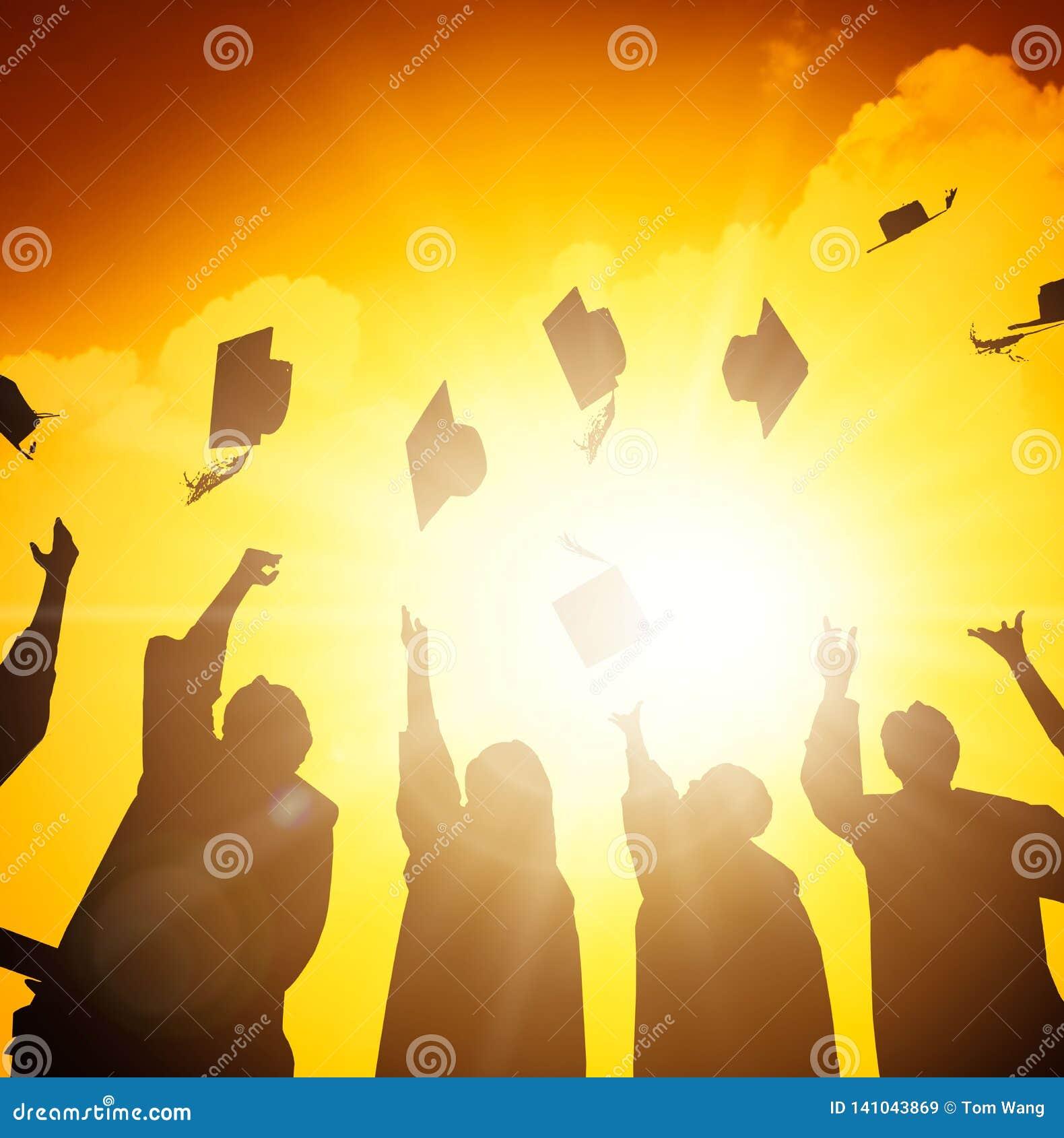 Estudantes que jogam tampões da graduação no ar