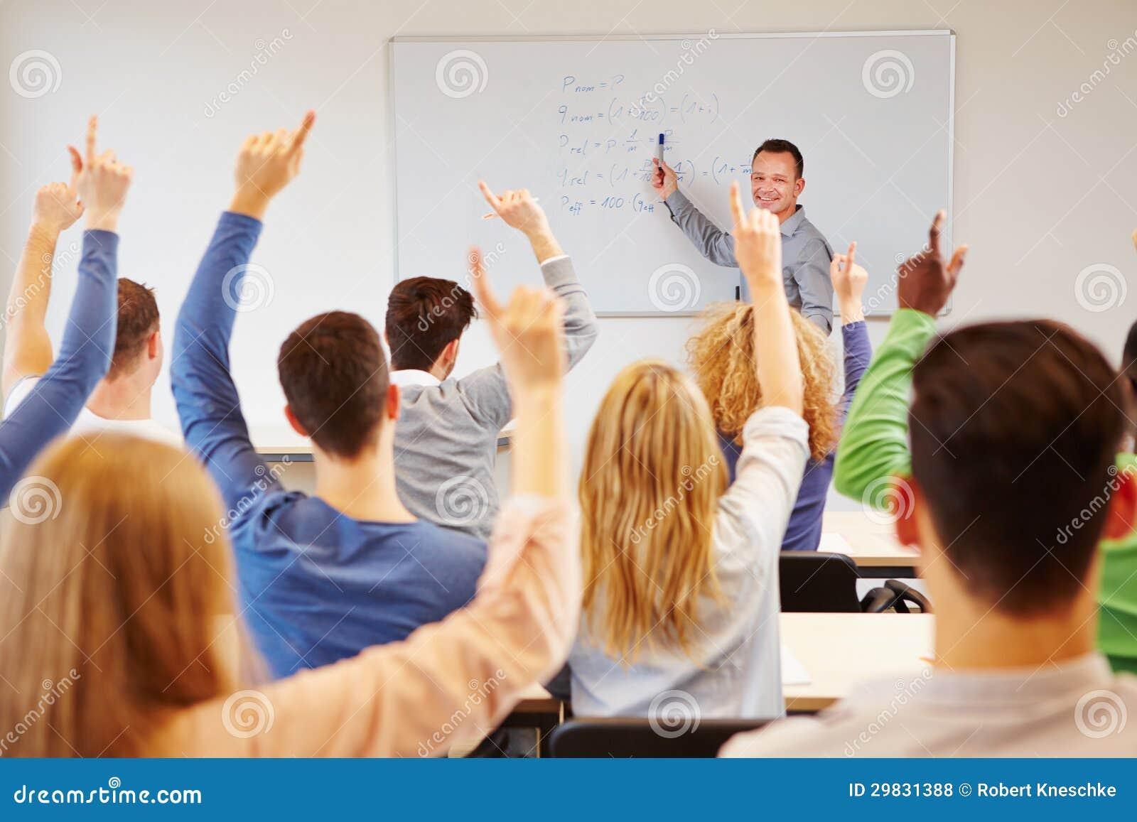 Estudantes que levantam as mãos na faculdade