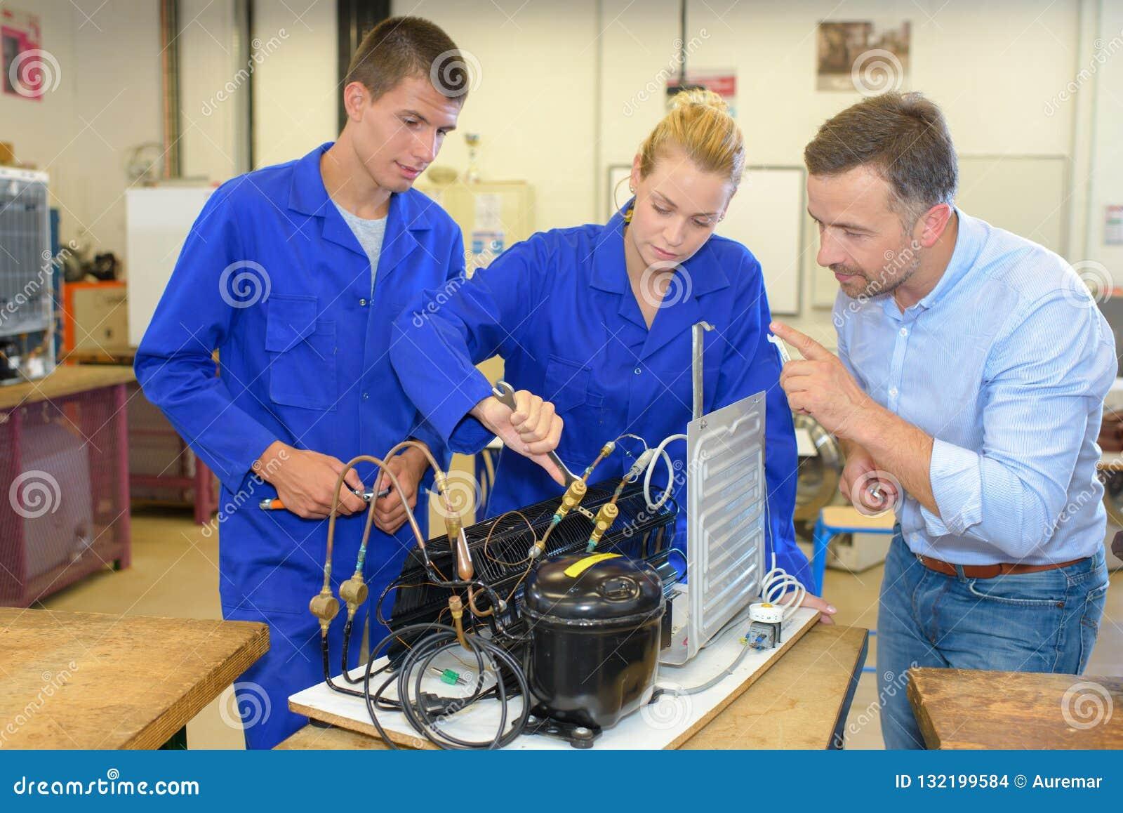 Estudantes que trabalham com componentes do radiador