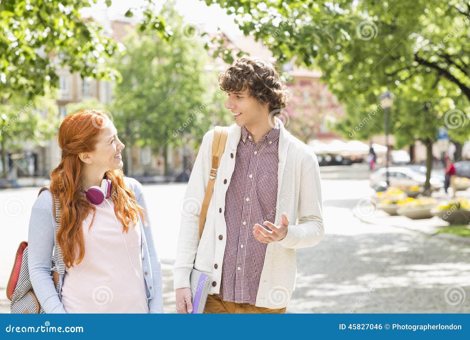 Estudantes universitário masculinas e fêmeas novas que falam ao andar no passeio