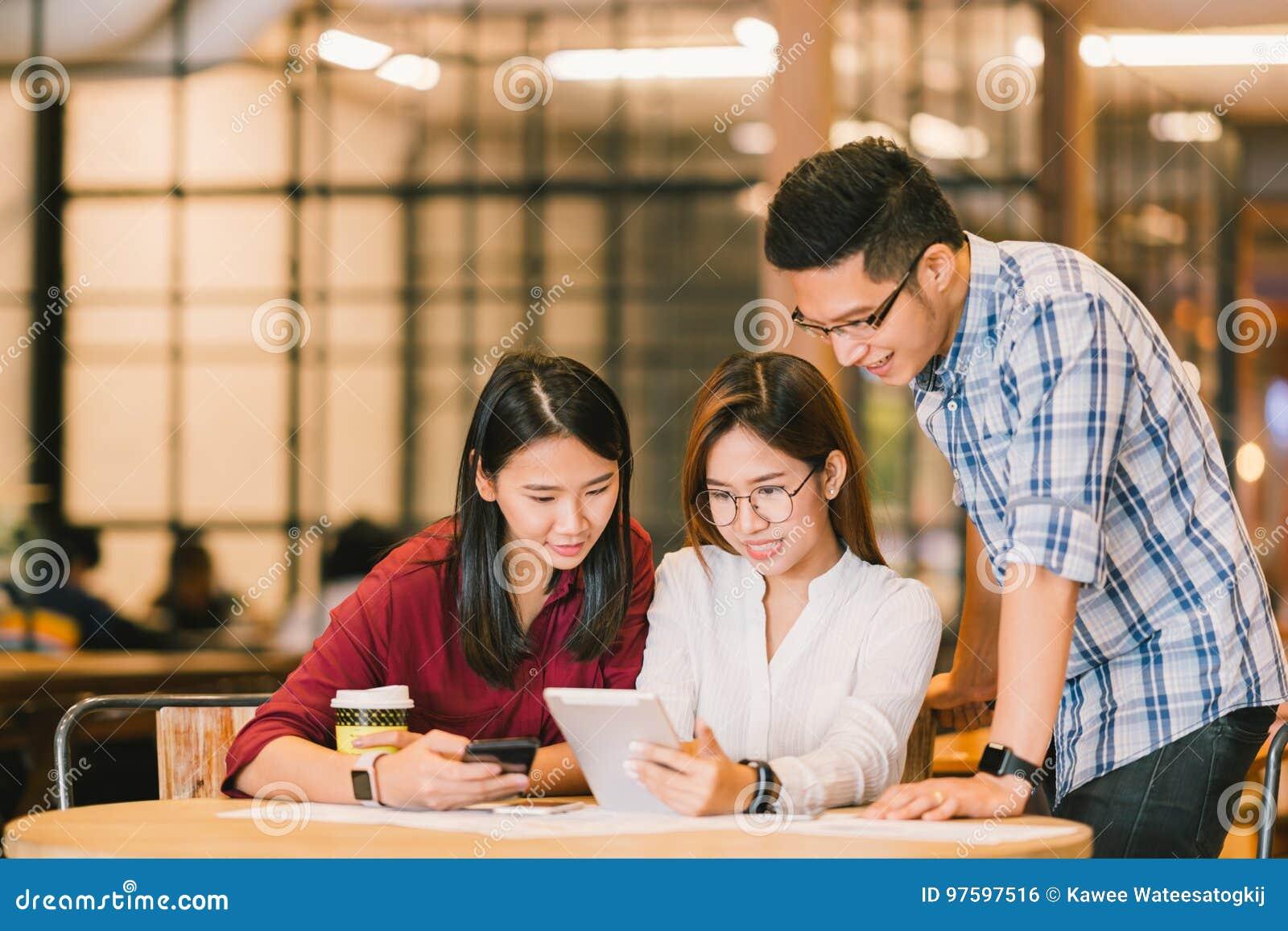 Estudantes universitário ou colegas de trabalho asiáticos que usam a tabuleta e o smartphone digitais junto na cafetaria