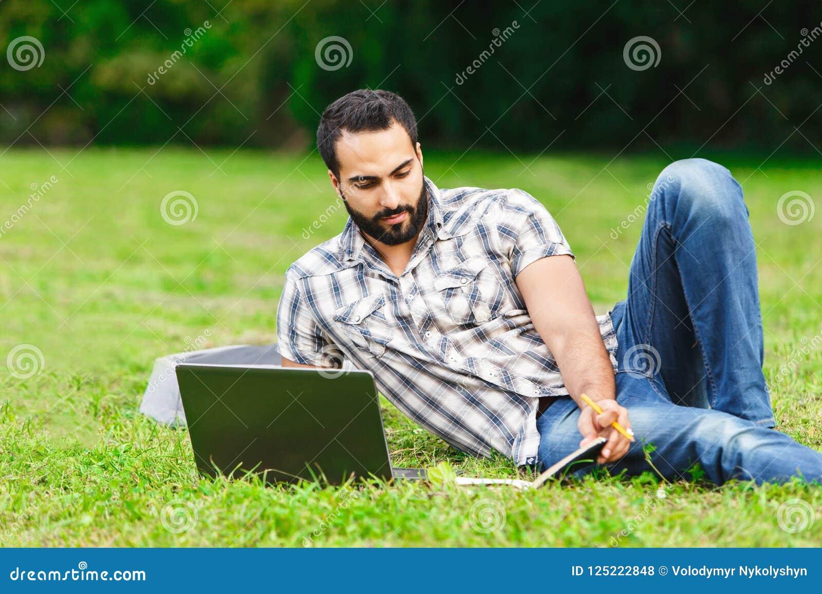 Estudiante barbudo Man Relaxing On la hierba