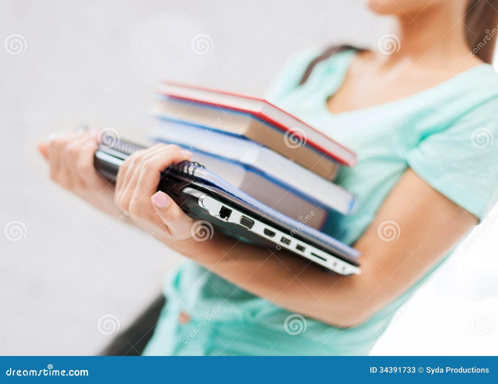 Estudiante con los libros, el ordenador y las carpetas