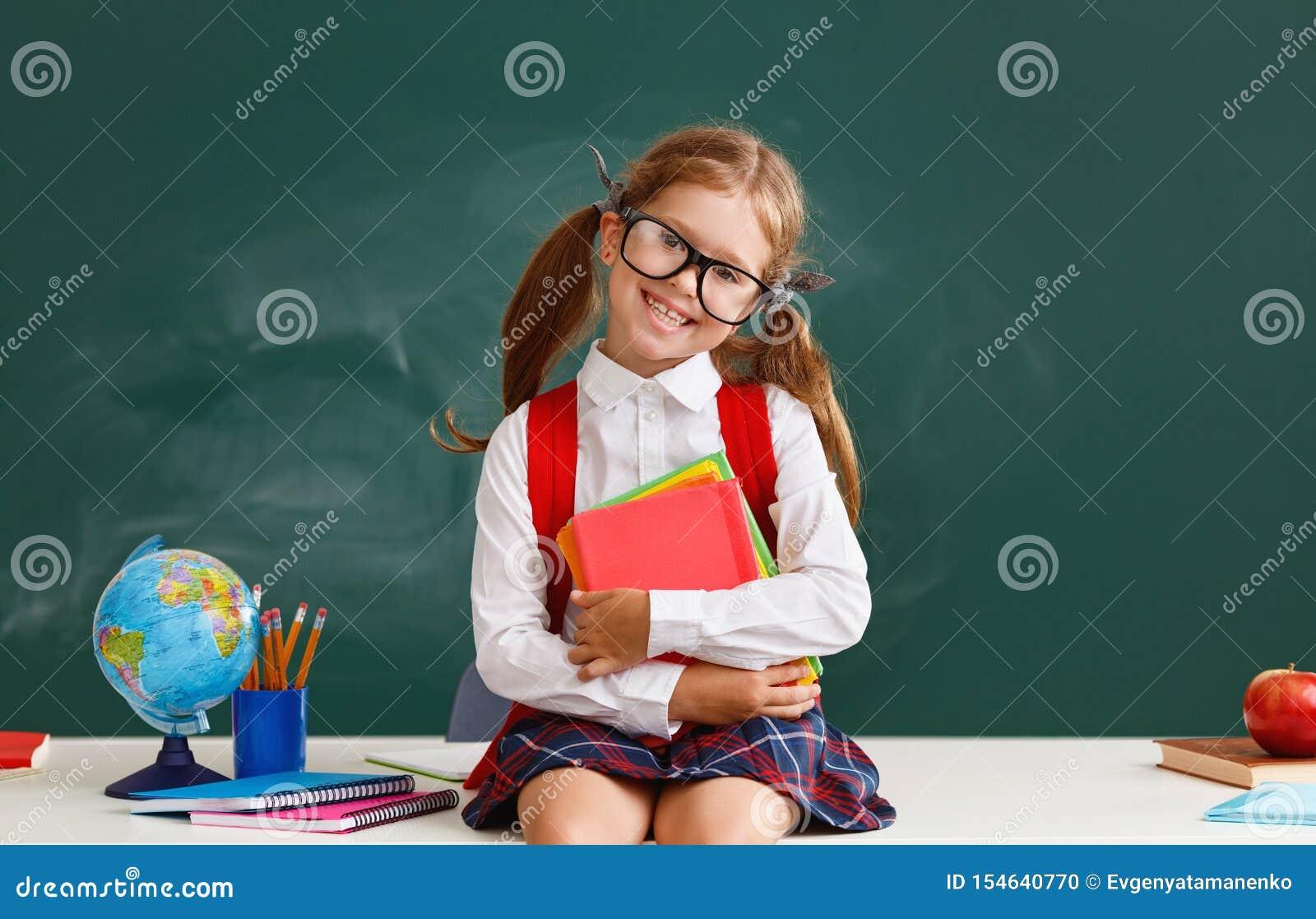 Estudiante divertida de la colegiala del niño sobre la pizarra de la escuela