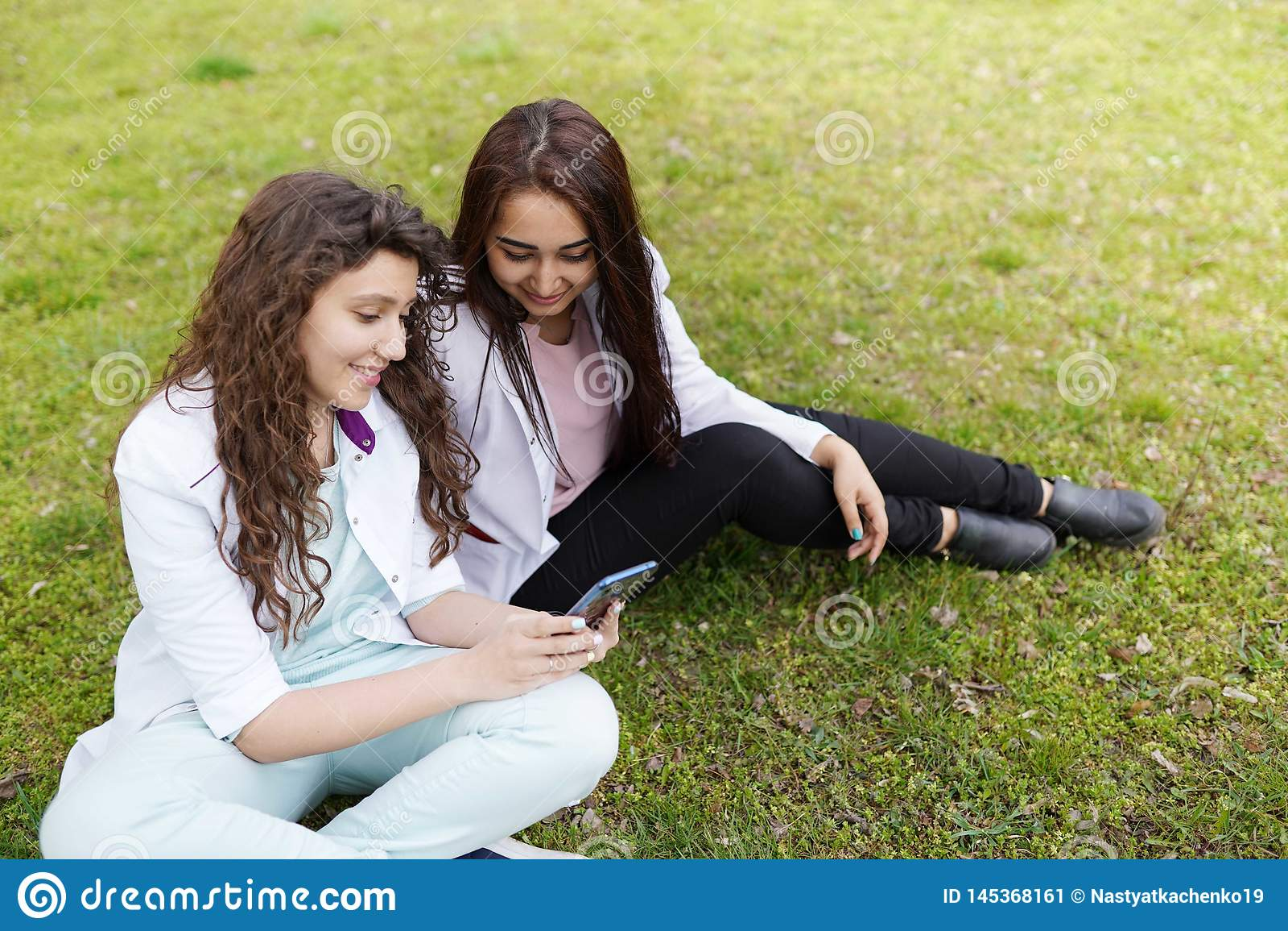 Estudiante femenino de los doctores al aire libre con el tel?fono Fondo m?dico estudiantes cerca del hospital en jard?n de flores