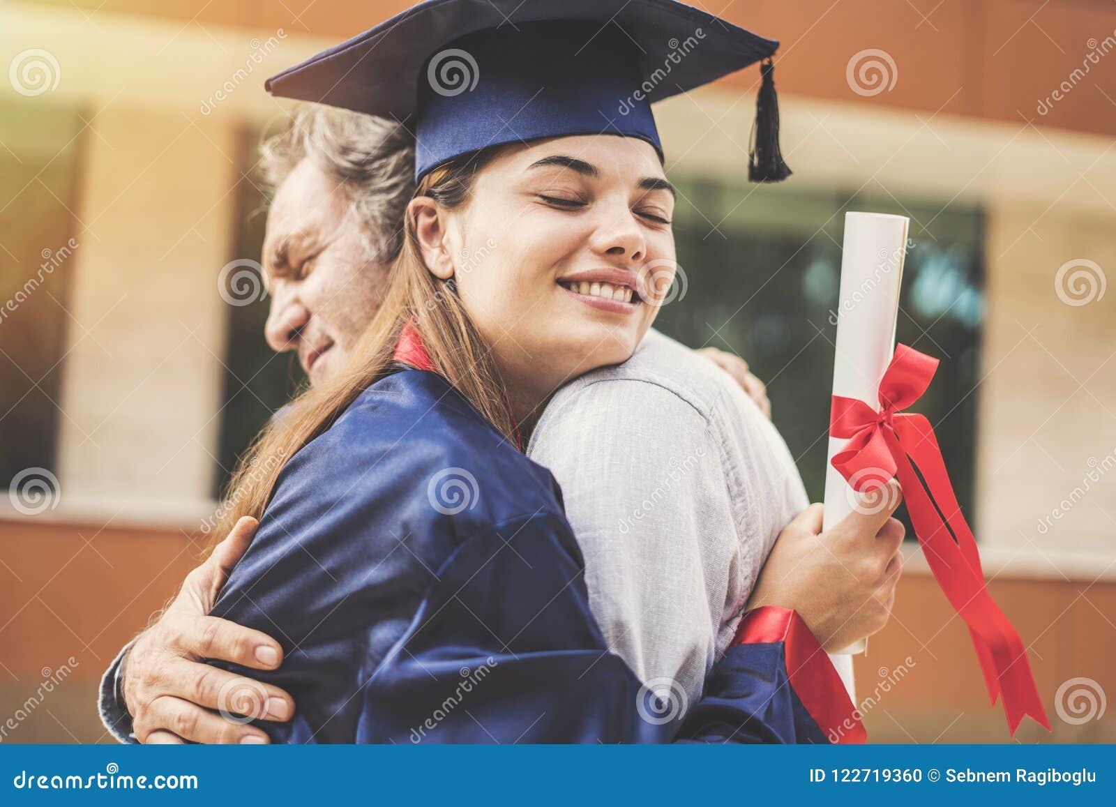 Estudiante graduado que abraza a su padre