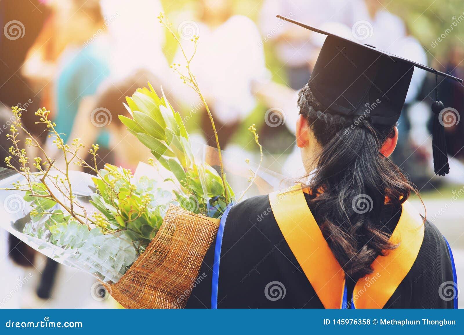 Estudiante joven del lado trasero del tiro a disposición que sostiene un ramo de flores los graduados de los sombreros de la grad