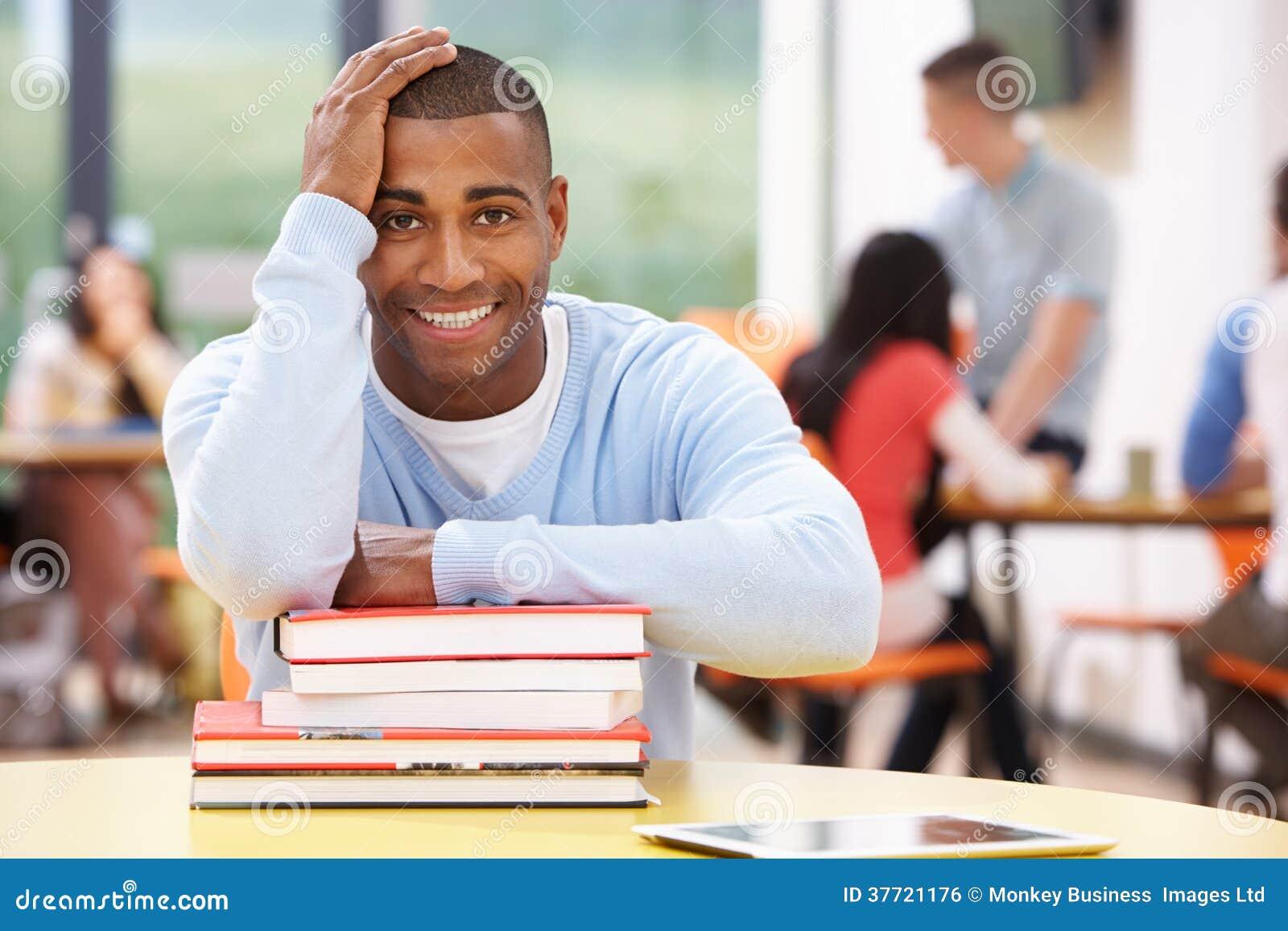Estudiante masculino Studying In Classroom con los libros