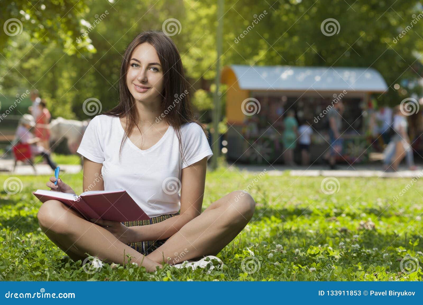 Estudiante moreno Girl Sitting en hierba verde en parque