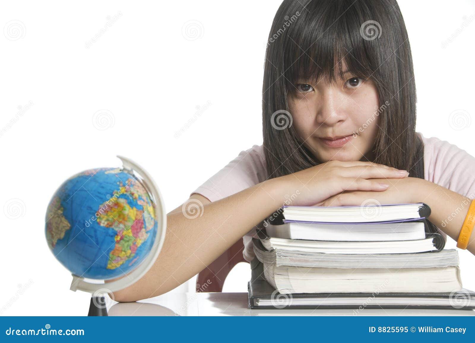 Estudiante que estudia con los libros y el globo