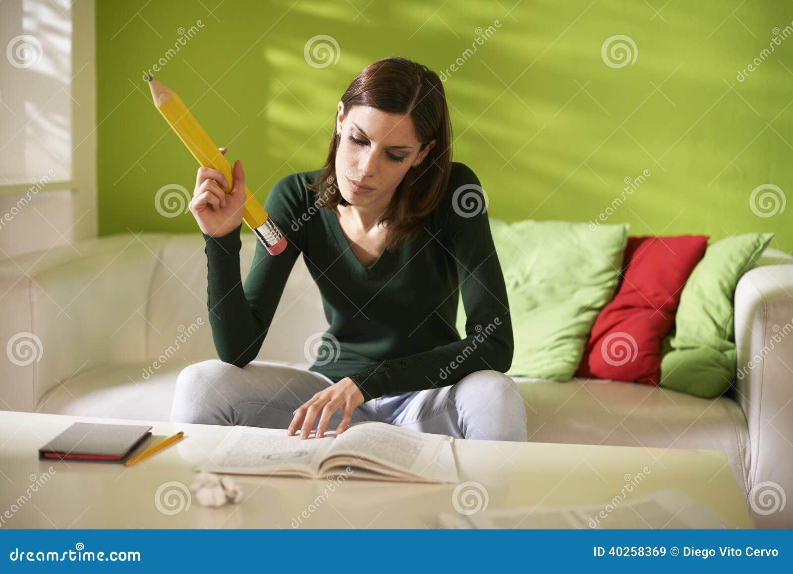 Estudiante que hace homeworks con el lápiz grande