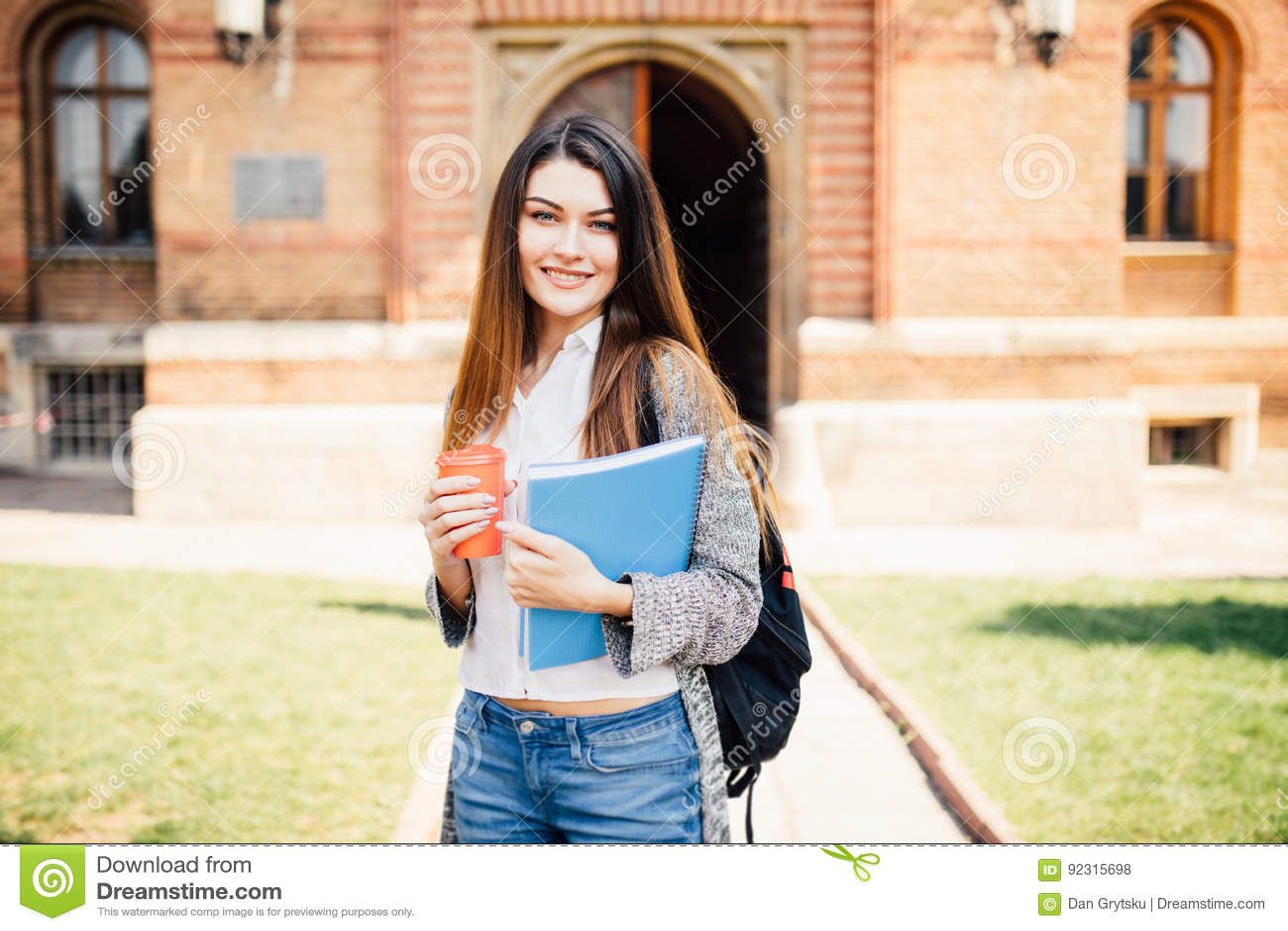 Estudiante universitario americano que sonríe con café y la bolsa de libros en campus