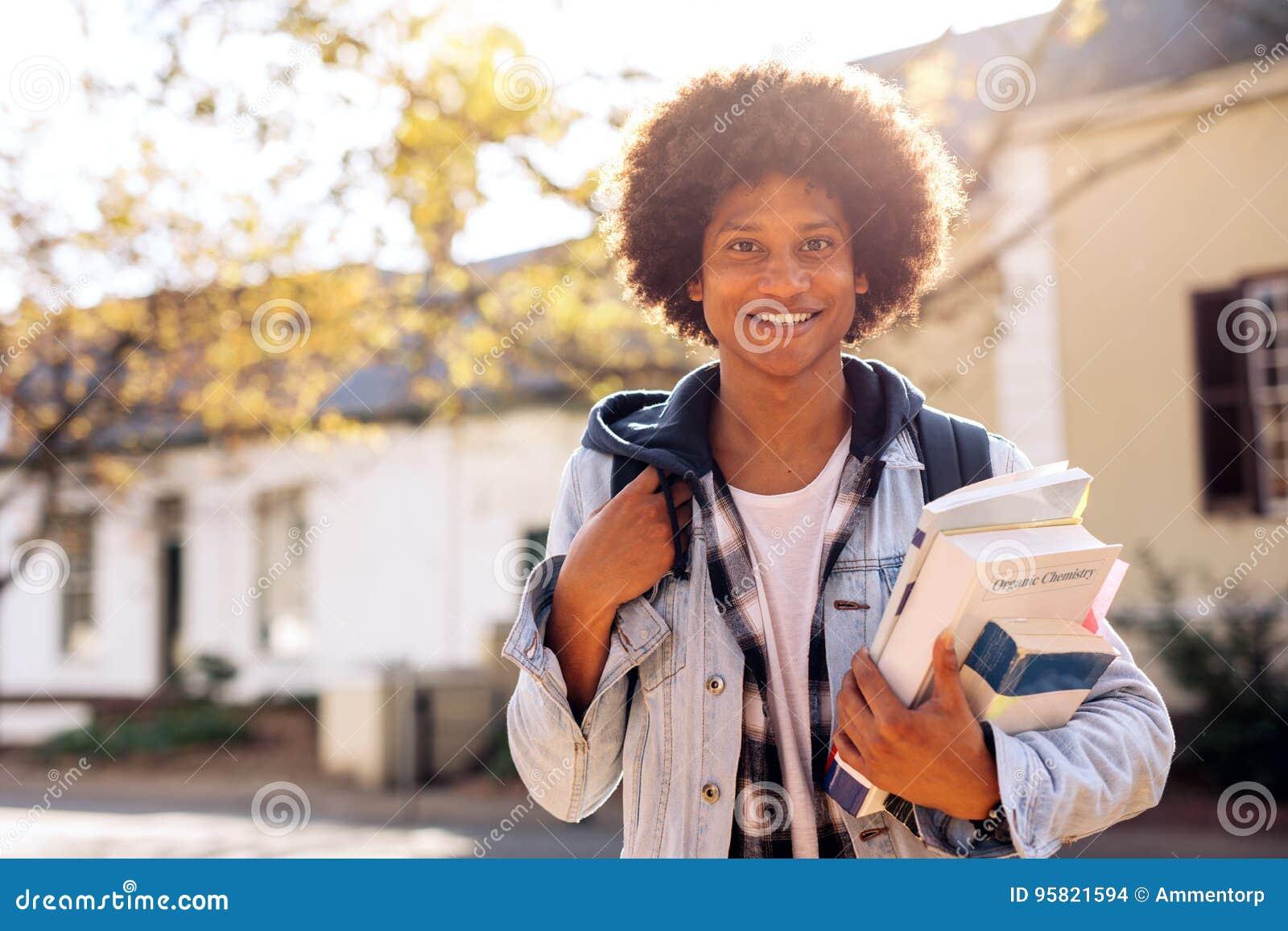 Estudiante universitario con las porciones de libros en campus de la universidad
