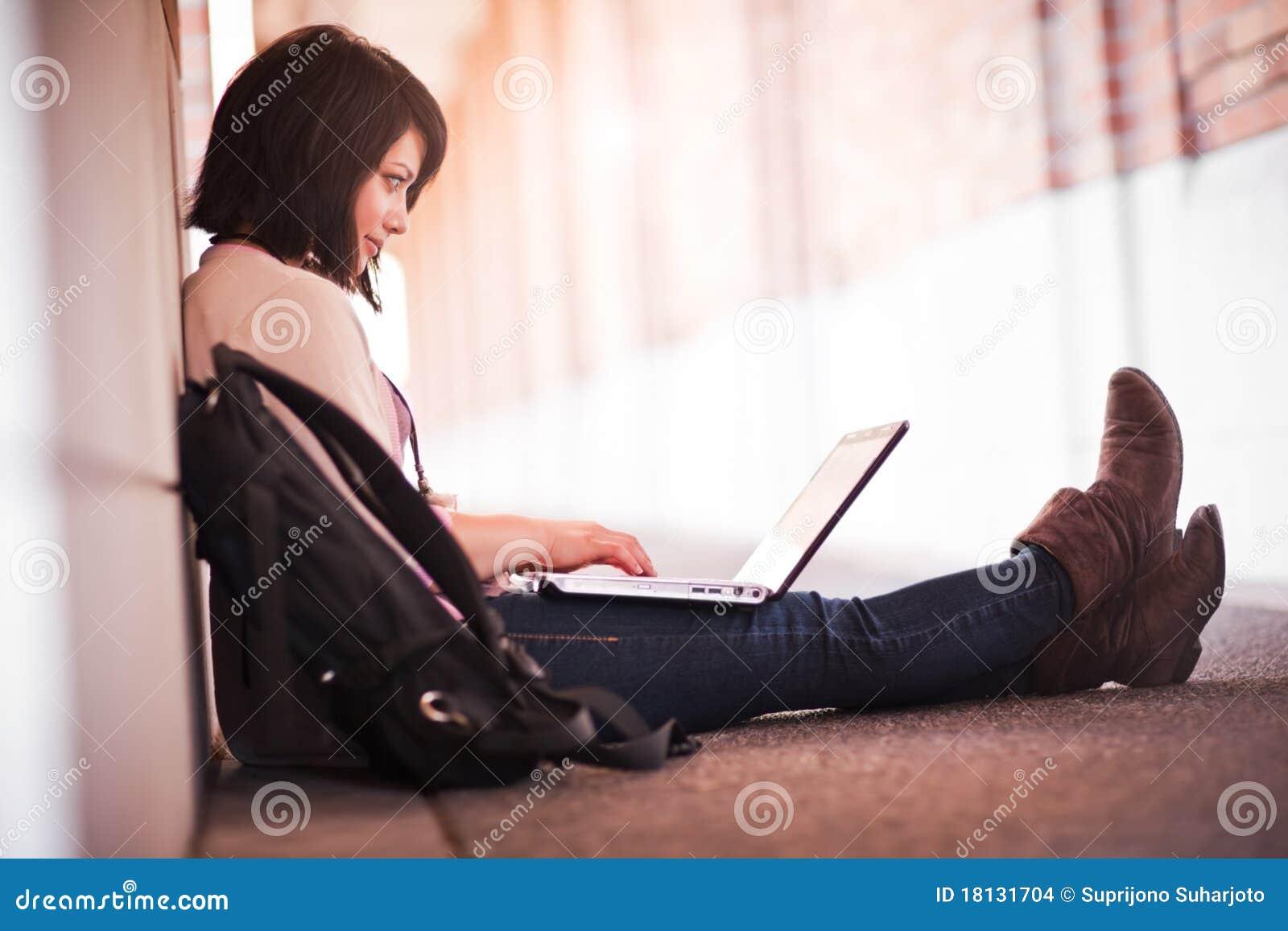 Estudiante universitario de la raza mezclada con la computadora portátil