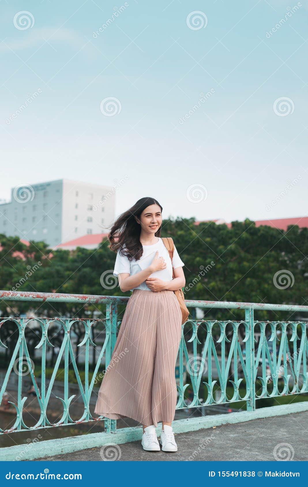 Estudiante universitario de sexo femenino asiático hermoso que sostiene sus libros que se colocan al aire libre, concepto de la u