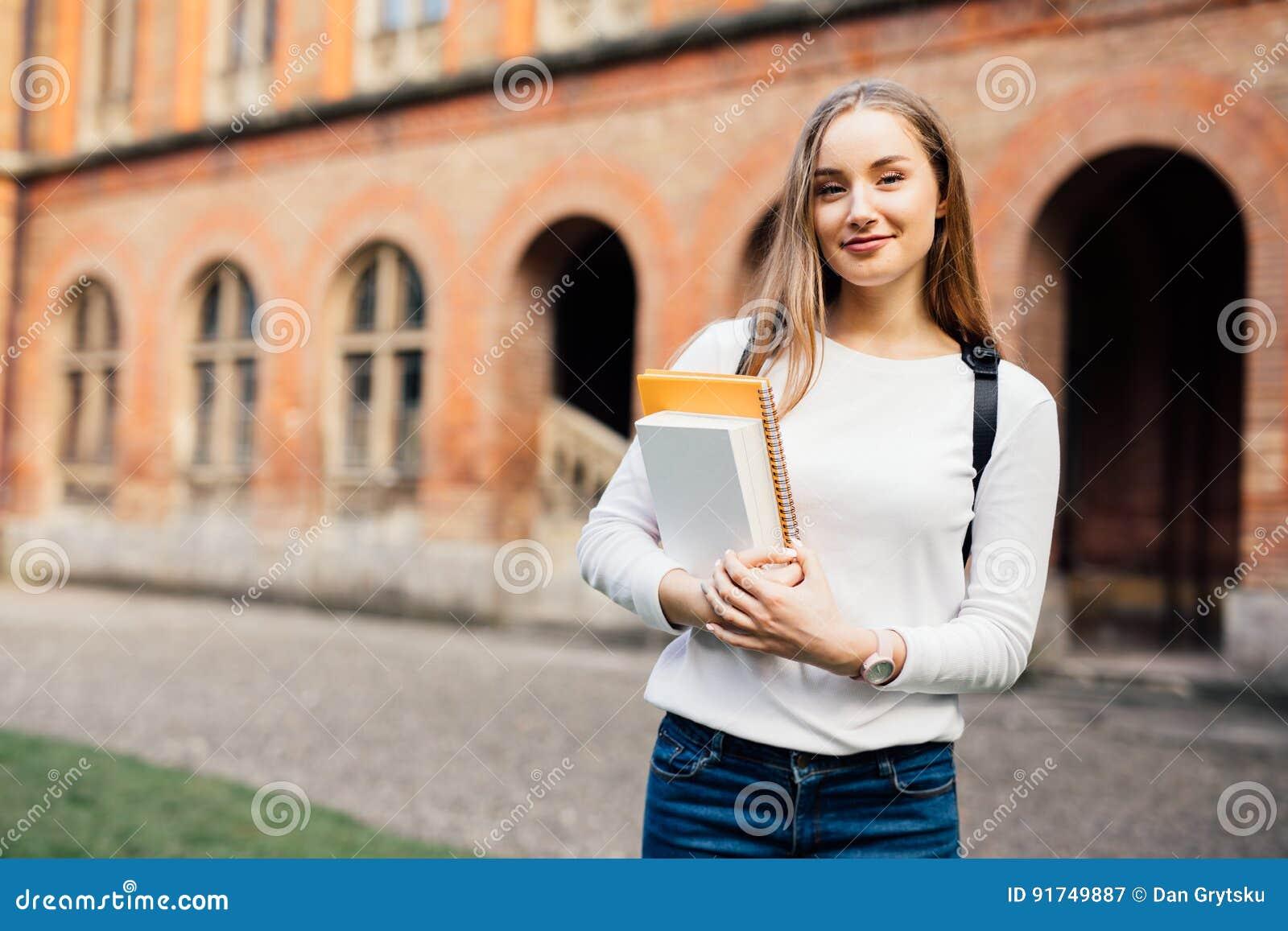 Estudiante universitario de sexo femenino Muchacha feliz en la universidad europea para la beca