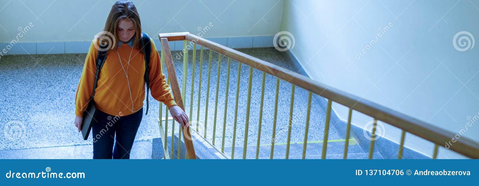 Estudiante universitario de sexo femenino solo deprimido joven que camina abajo de las escaleras en su escuela, mirando abajo Edu