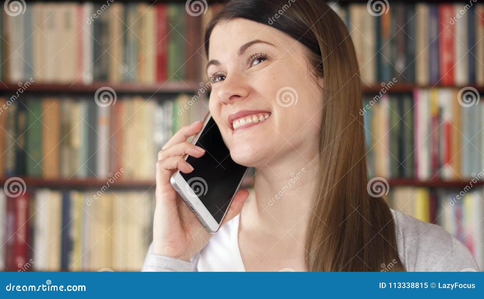 ced308ea3f716 Estudiante Universitario De Sexo Femenino Sonriente Que Usa El Teléfono  Móvil En La Biblioteca De Universidad