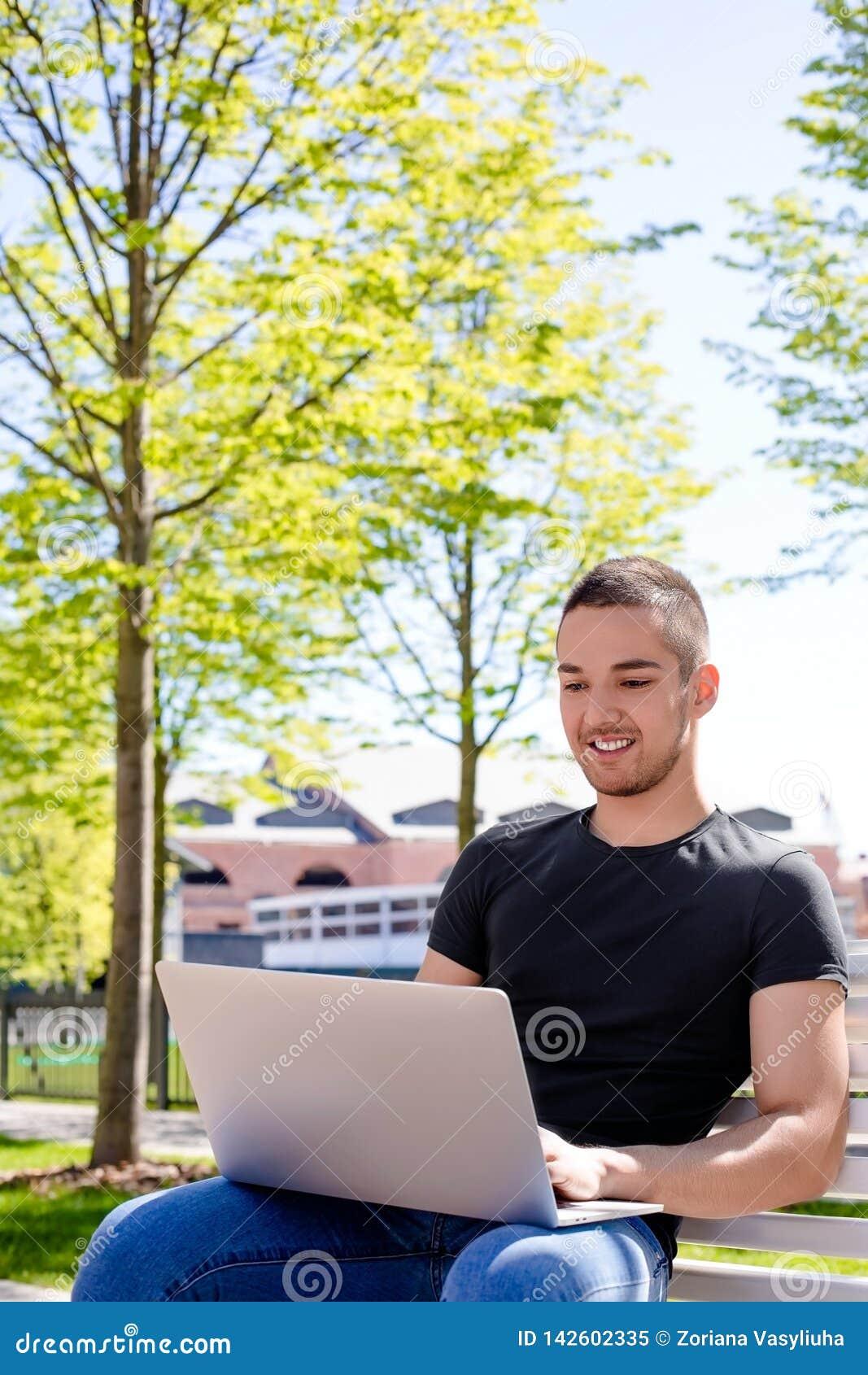 Estudiante universitario de sexo masculino alegre que tiene educación en línea vía el netbook, sentándose en un campus