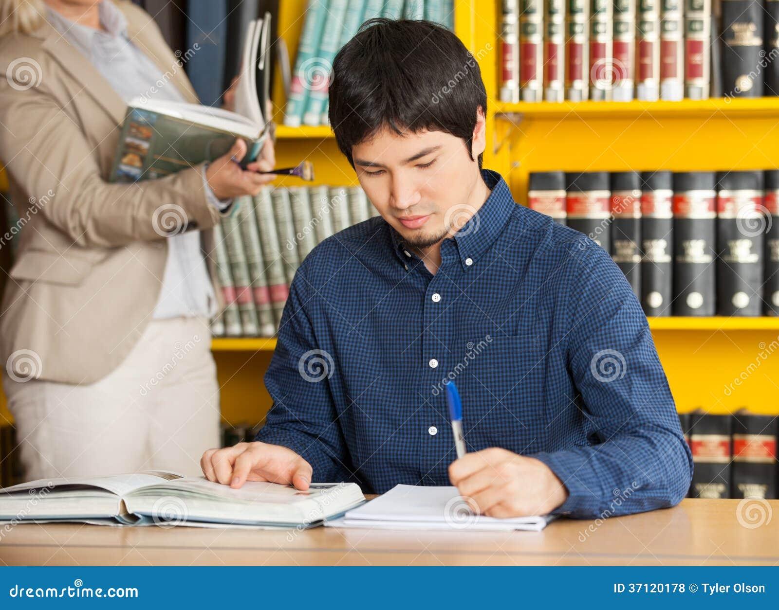Estudiante Writing In Book en la biblioteca de universidad