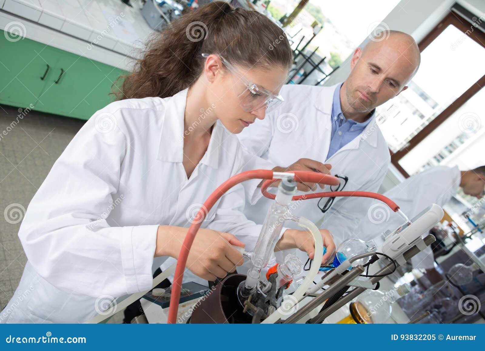 Estudiante y profesor que trabajan en el brazo robótico junto