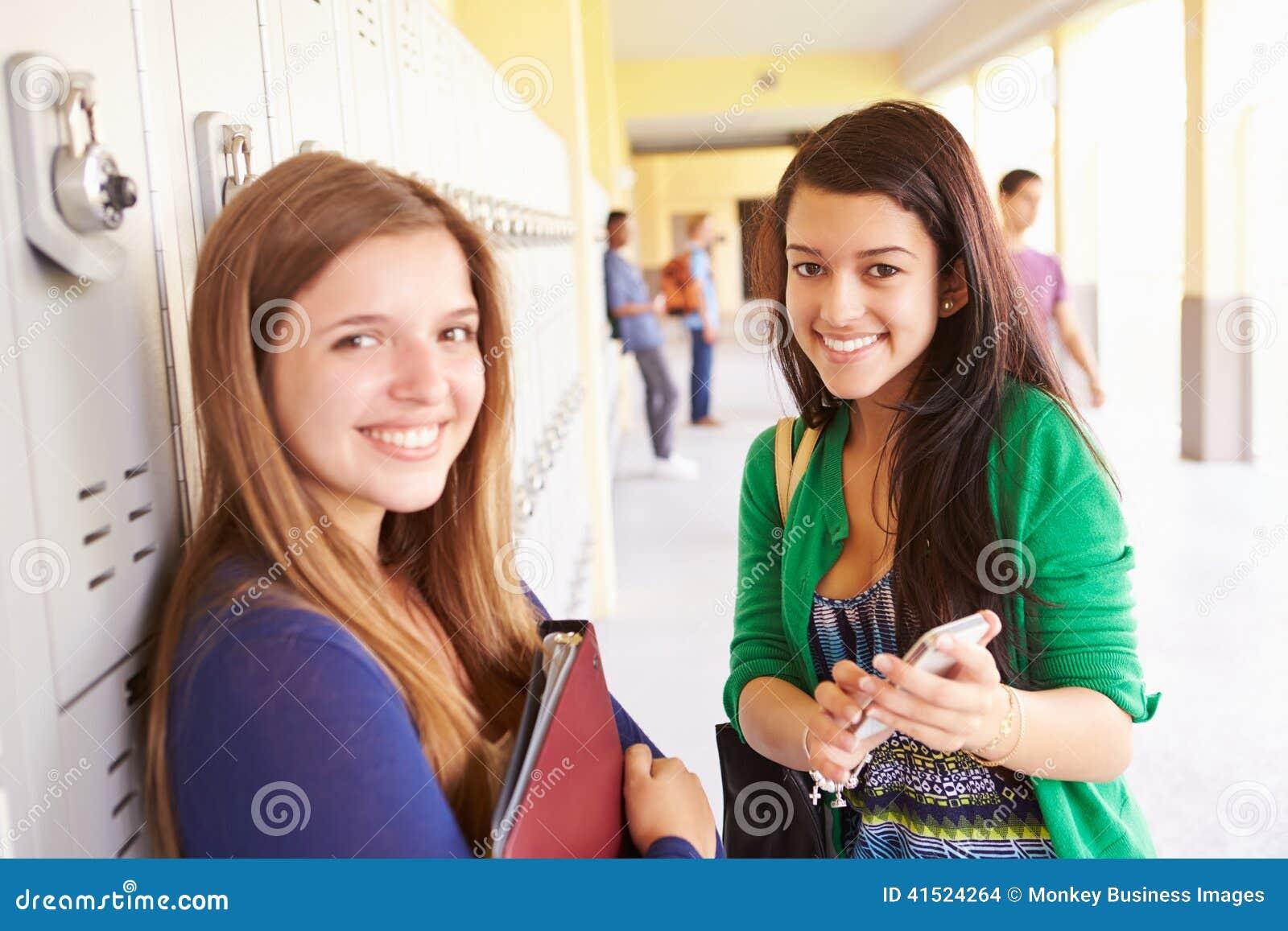 Estudiantes de la High School secundaria por los armarios que miran el teléfono móvil