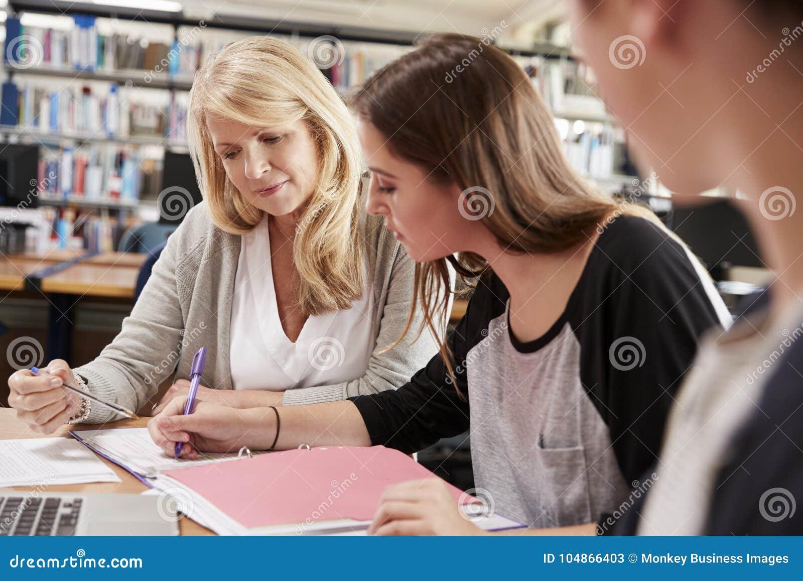 Estudiantes de Working With College del profesor de sexo femenino en biblioteca