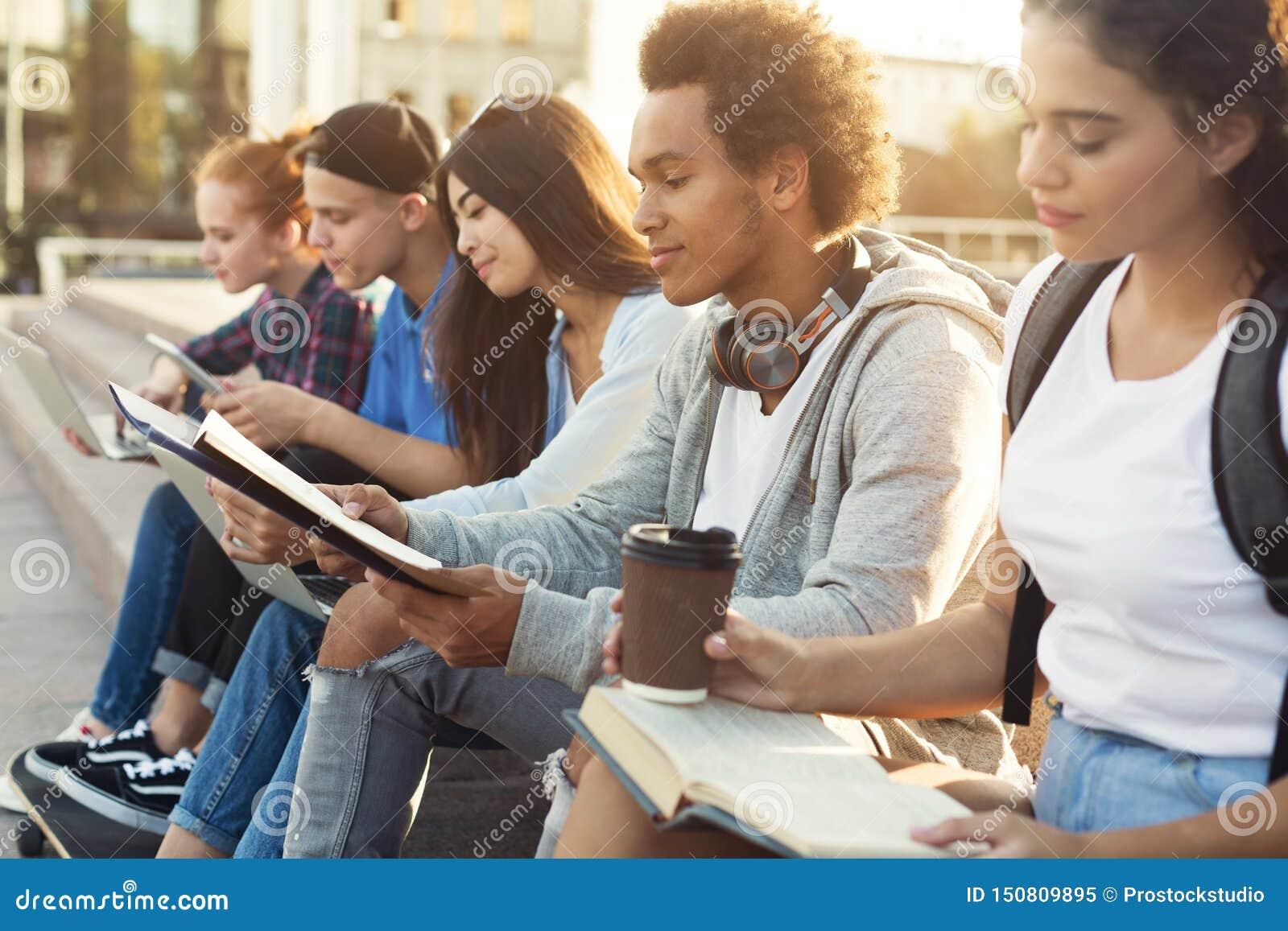 Estudiantes diversos adolescentes que estudian al aire libre por la tarde