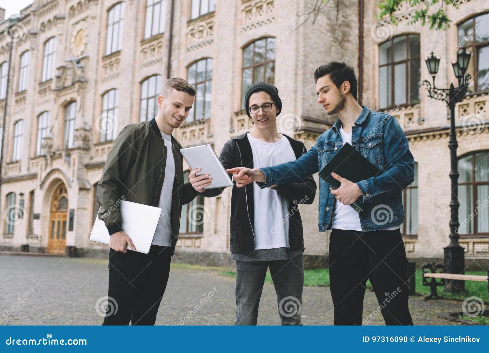 Estudiantes felices acertados que colocan el campus o la universidad cercano afuera