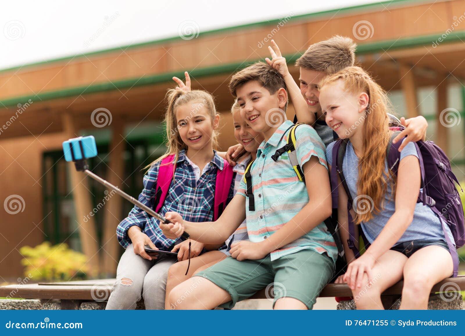 Estudiantes felices de la escuela primaria que toman el selfie