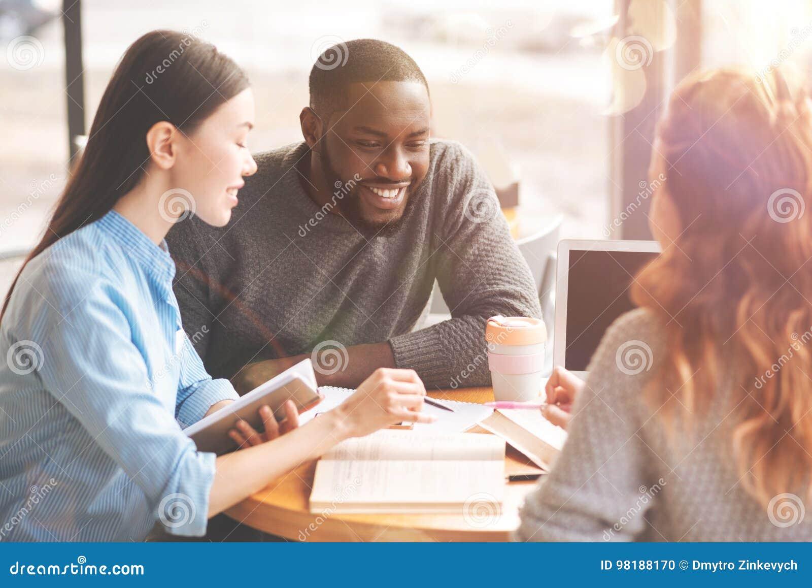 Estudiantes internacionales positivos que estudian en el café