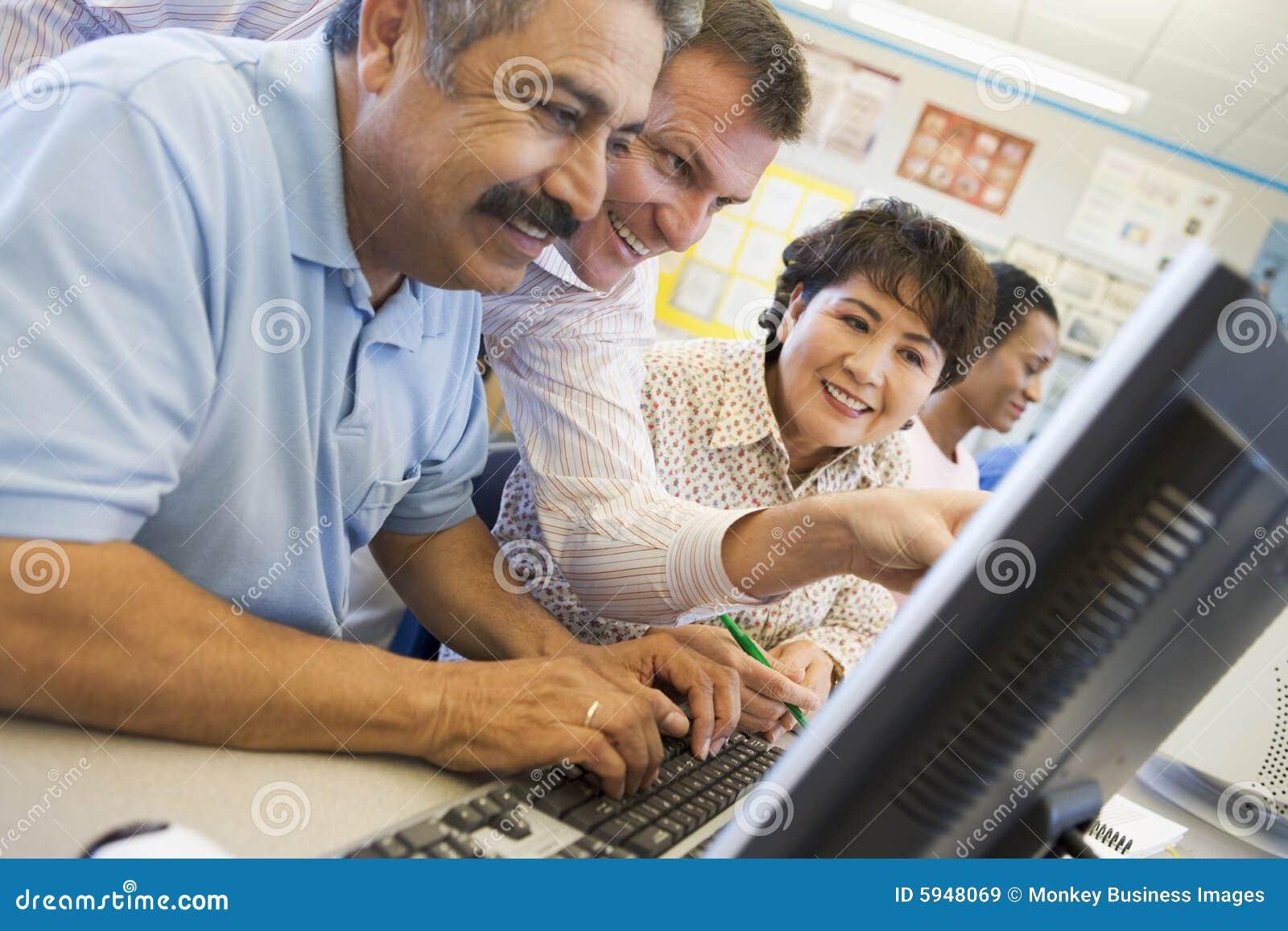 Estudiantes maduros que aprenden destrezas del ordenador