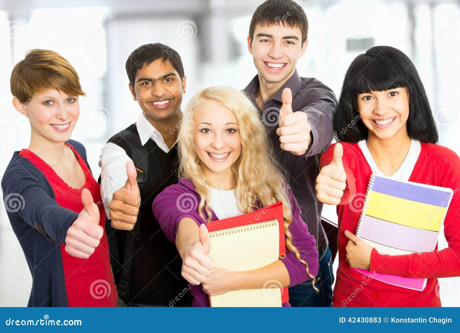 Estudiantes que dan la muestra de los pulgares-para arriba