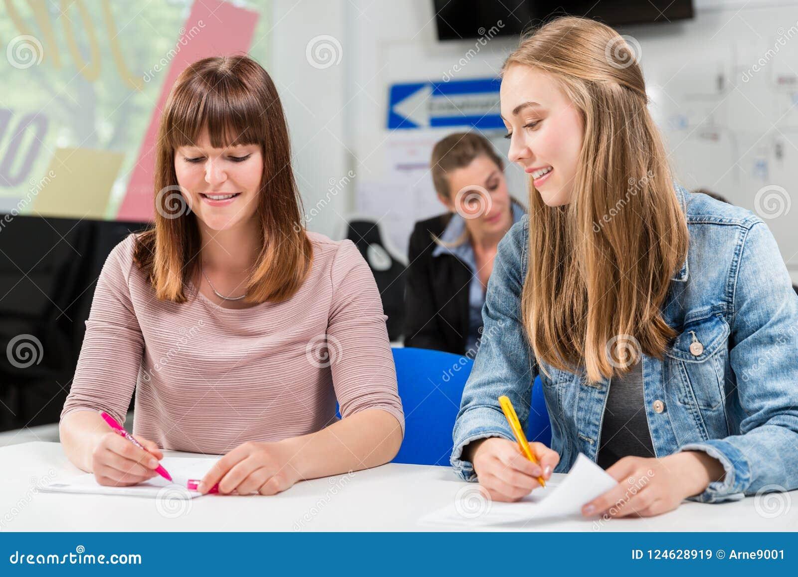 Estudiantes que escriben la prueba o el examen después de acabar sus lecciones de conducción