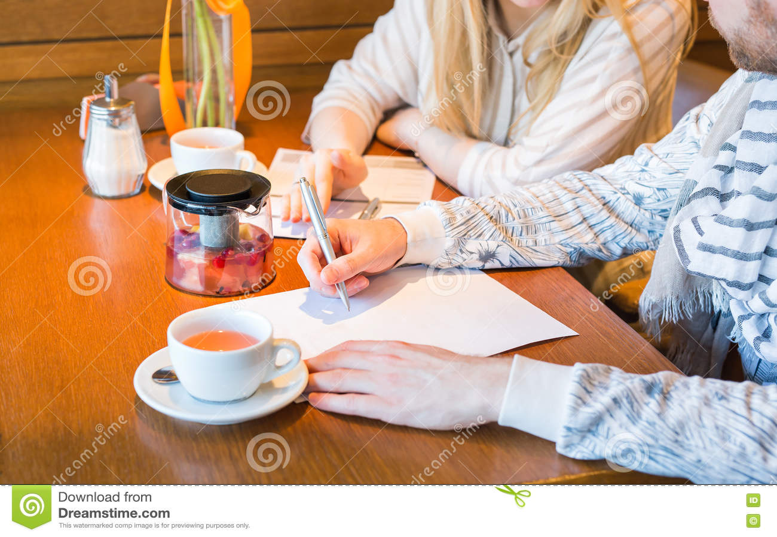 Estudiantes que hacen la preparación y que preparan el examen en la universidad, primer de la escritura del hombre joven en bibli