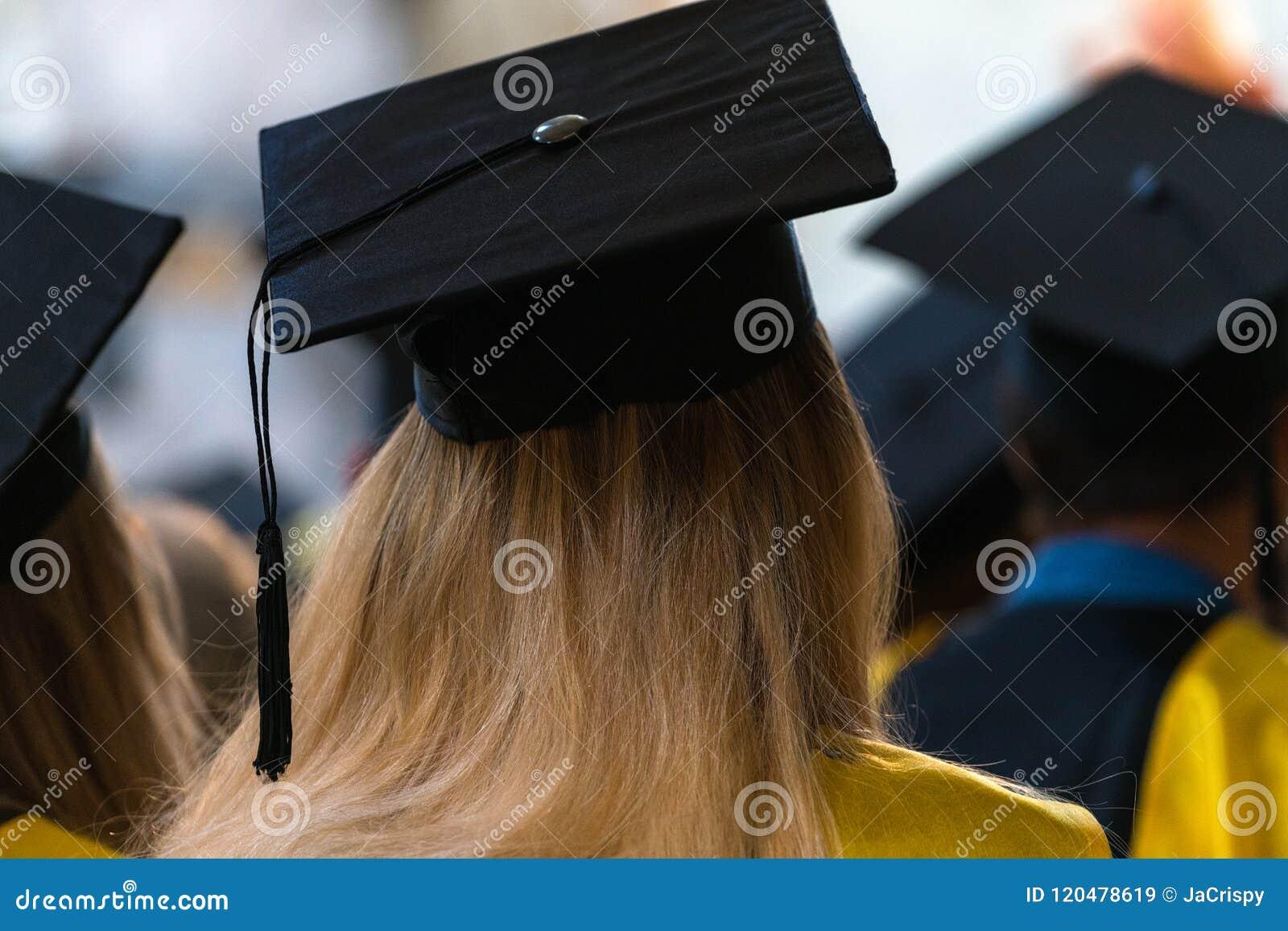 Estudiantes que llevan los vestidos y los sombreros que se sientan dentro, esperando al rece