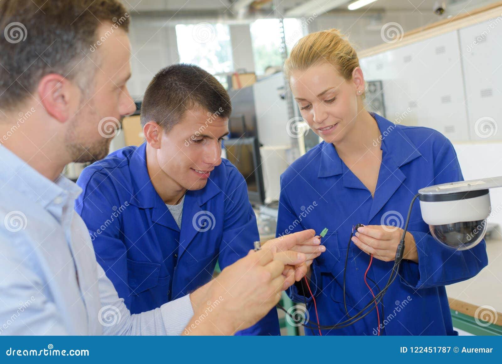 Estudiantes que miran los conectores de cable