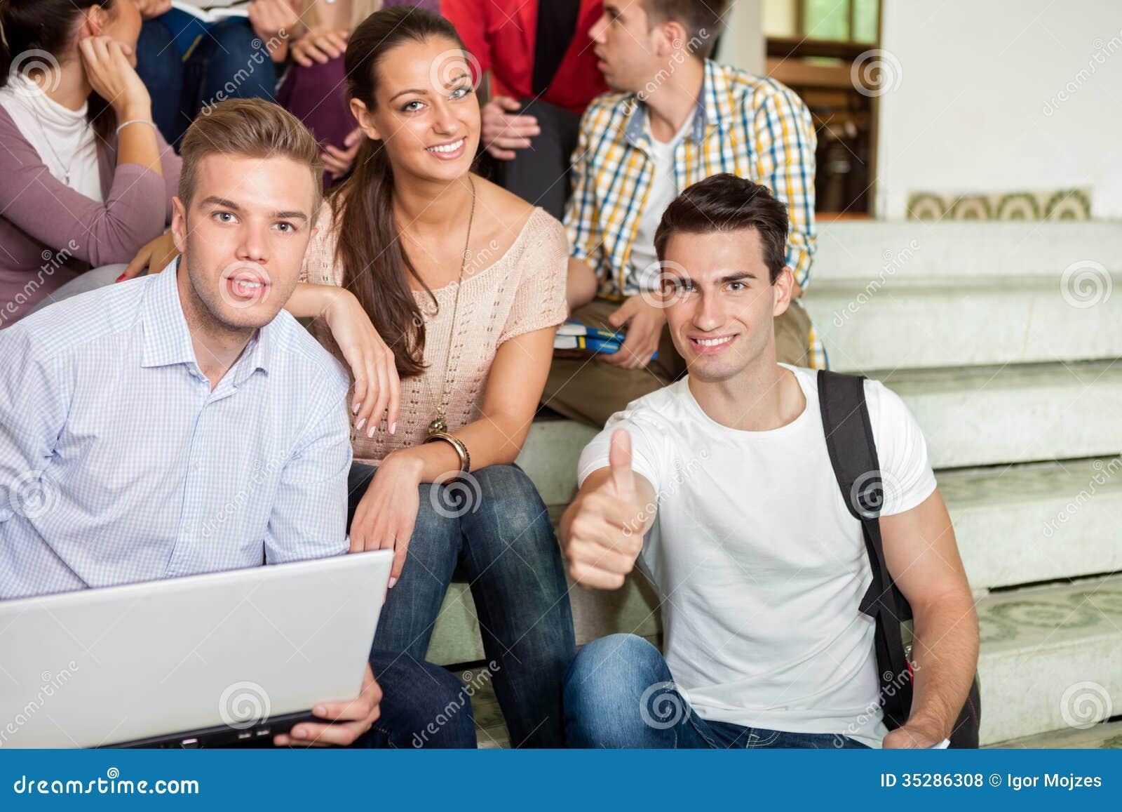 Estudiantes que se divierten con las escaleras de la escuela del ordenador portátil