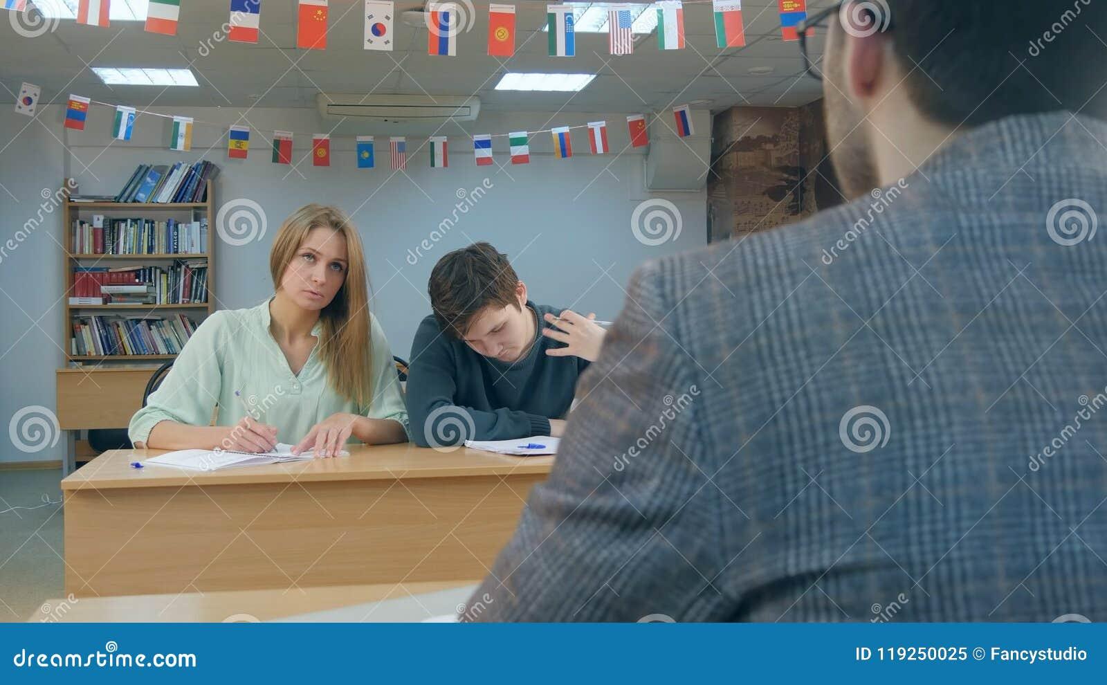 Estudiantes serios que se sientan para las notas de una escritura del examen