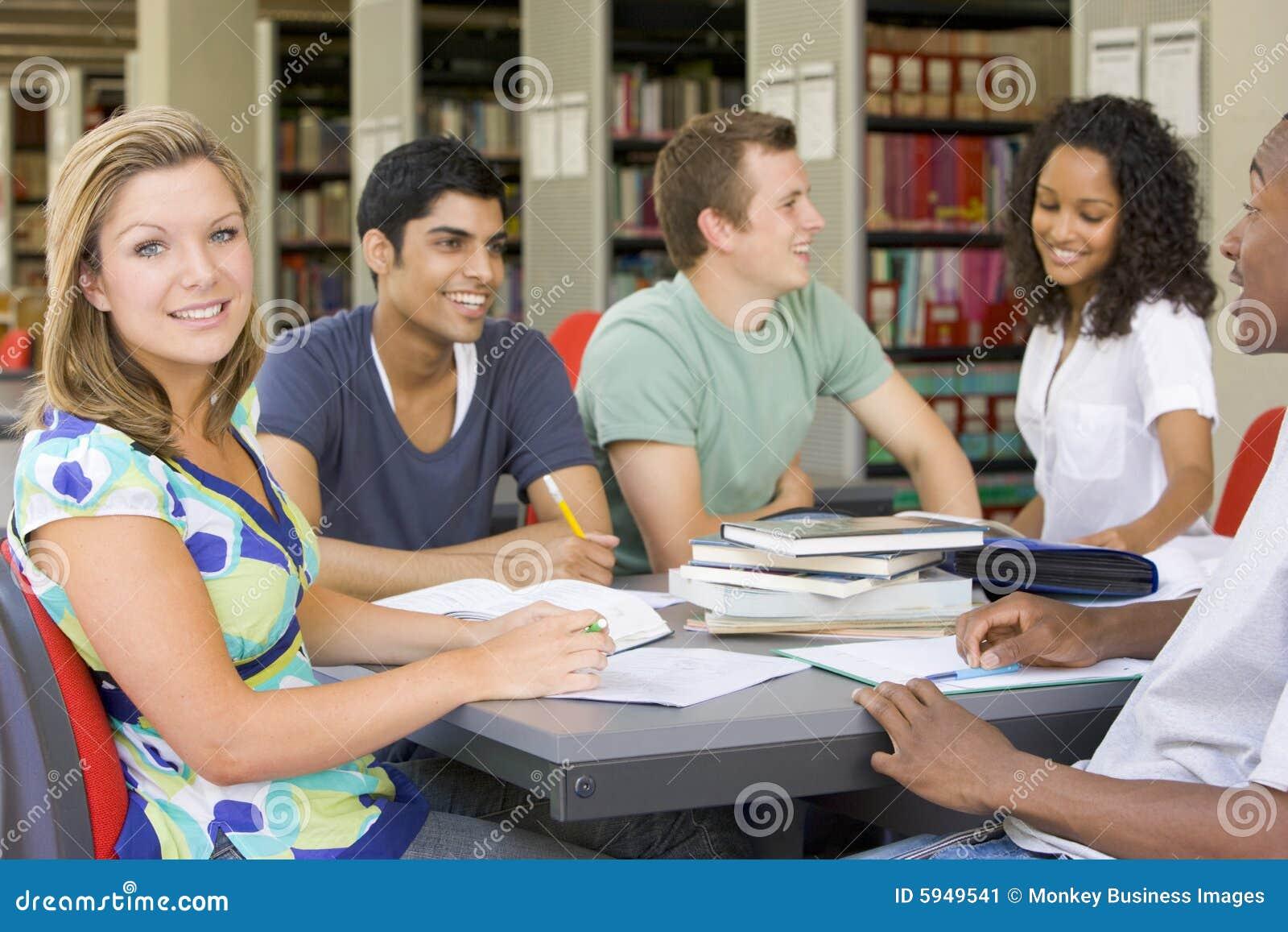 Estudiantes universitarios que estudian junto en una biblioteca