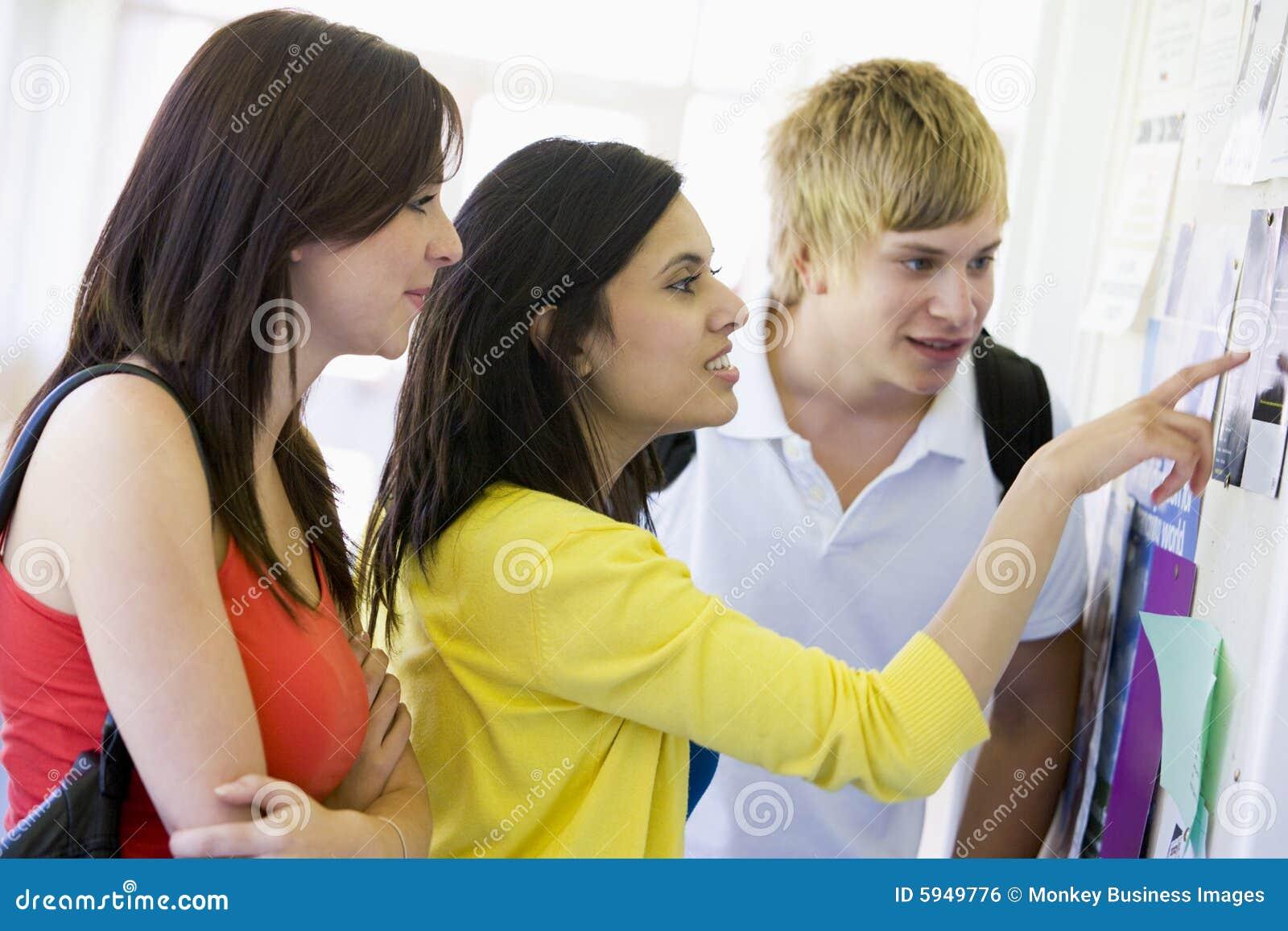 Estudiantes universitarios que miran un tablón de anuncios