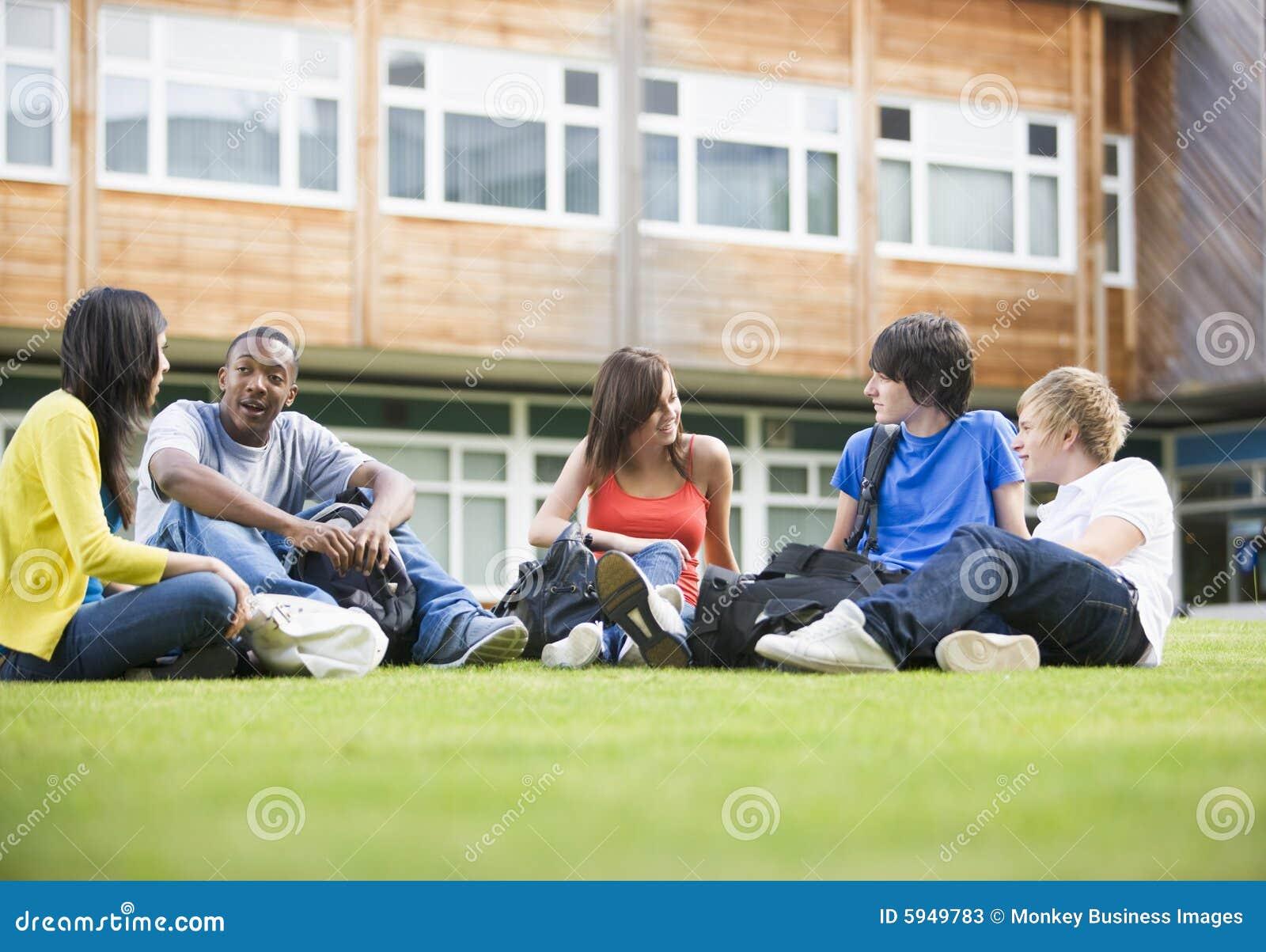 Estudiantes universitarios que se sientan y que hablan en césped