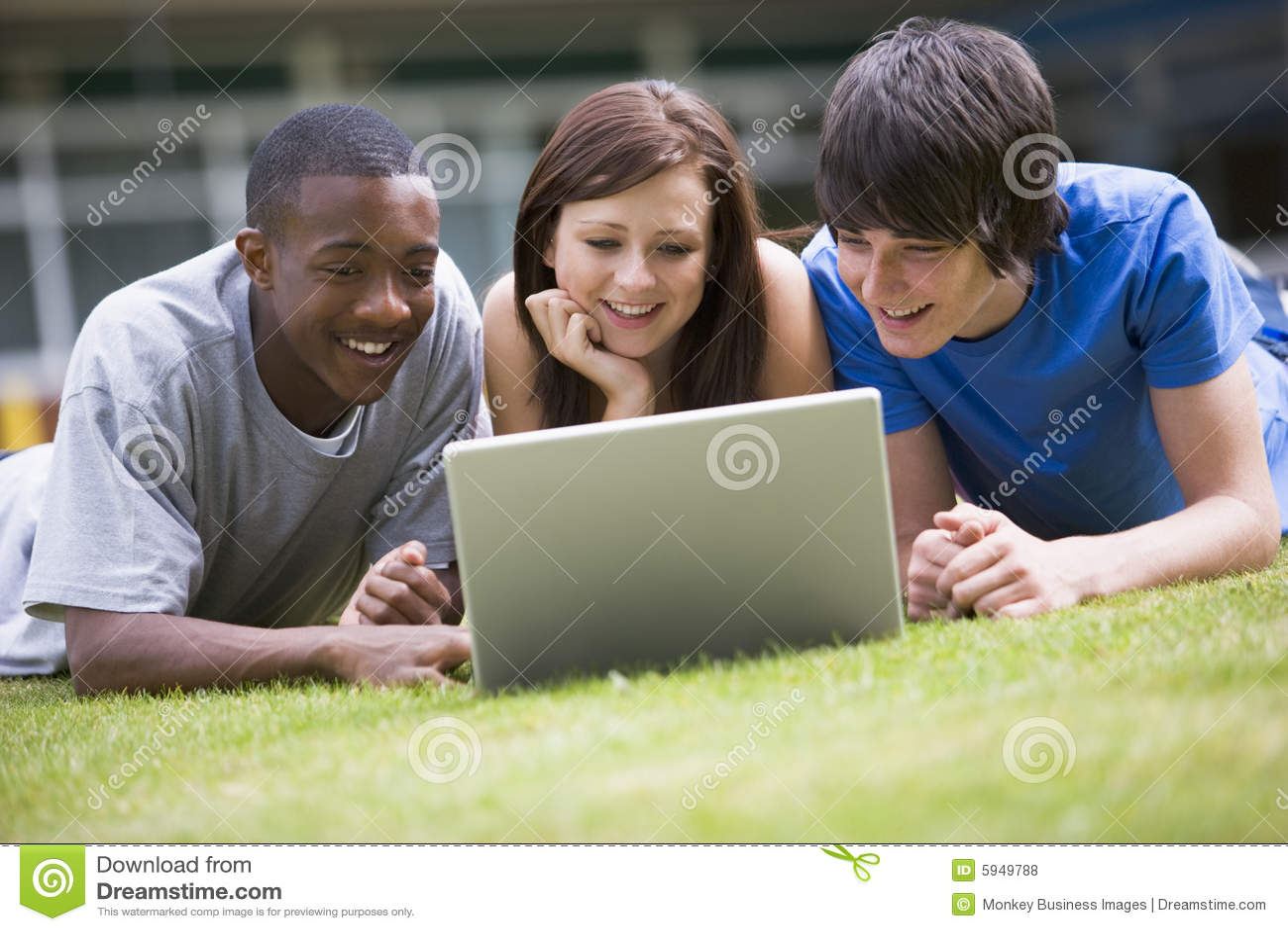 Estudiantes universitarios que usan la computadora portátil en césped del campus