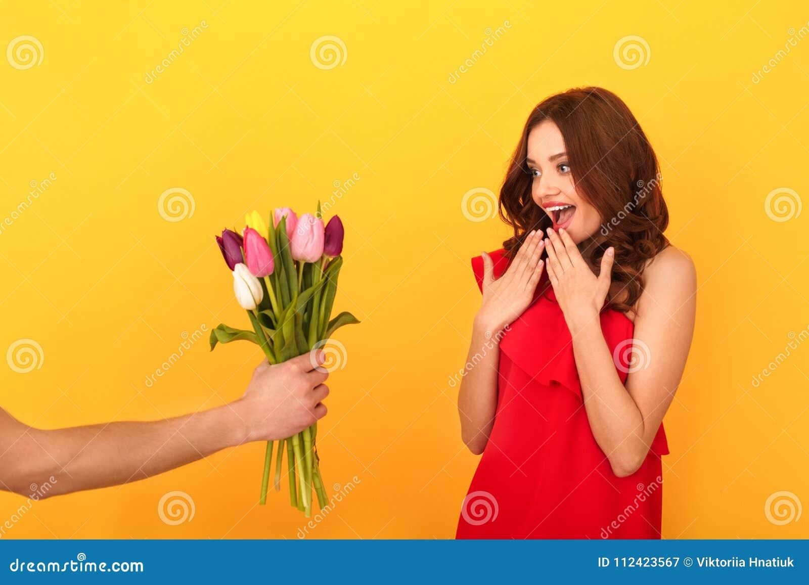 Estudio de la mujer joven aislado en amarillo en un vestido rojo que consigue a tulipanes el ramo
