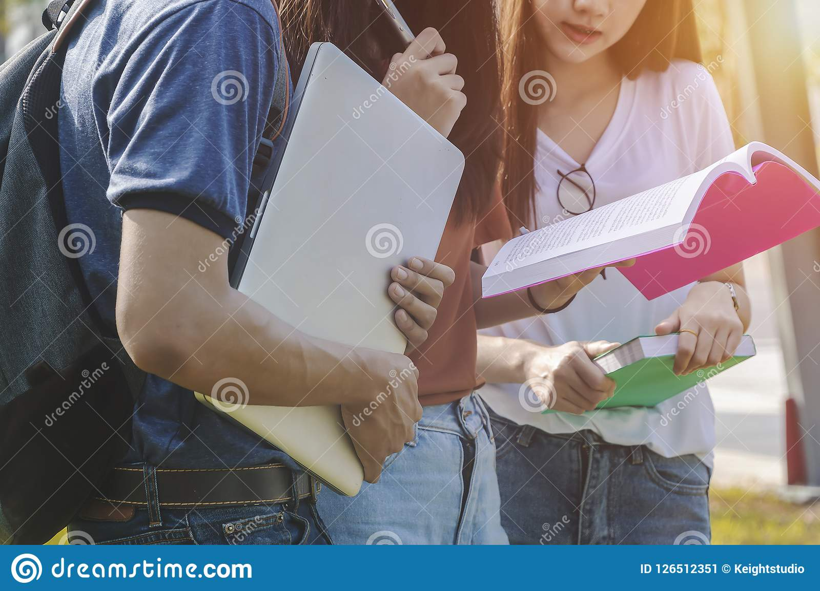 Estudo asiático do livro de leitura da educação do grupo que sorri com tabuleta, regaço