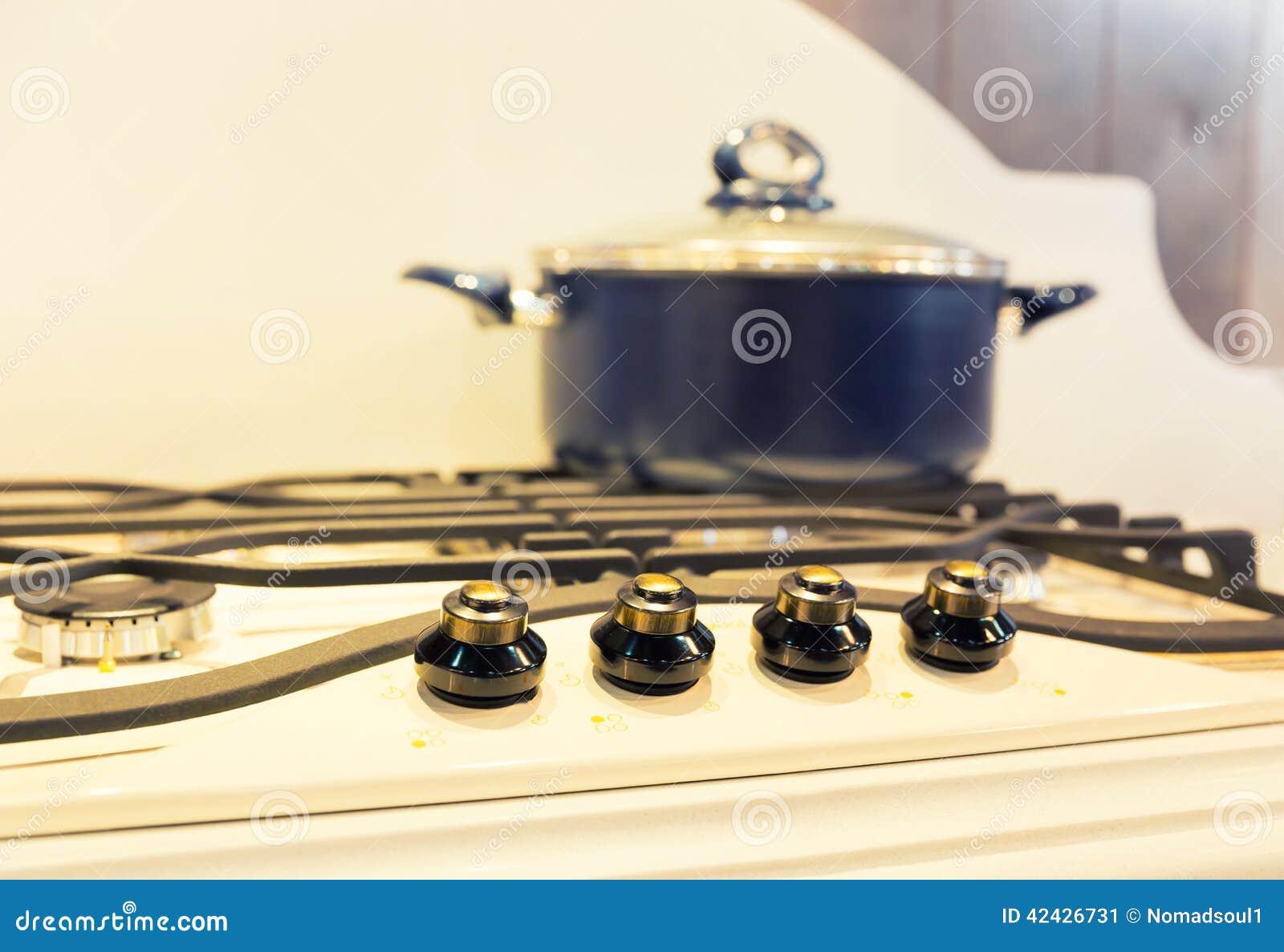 Estufa con el cazo en la cocina moderna blanca