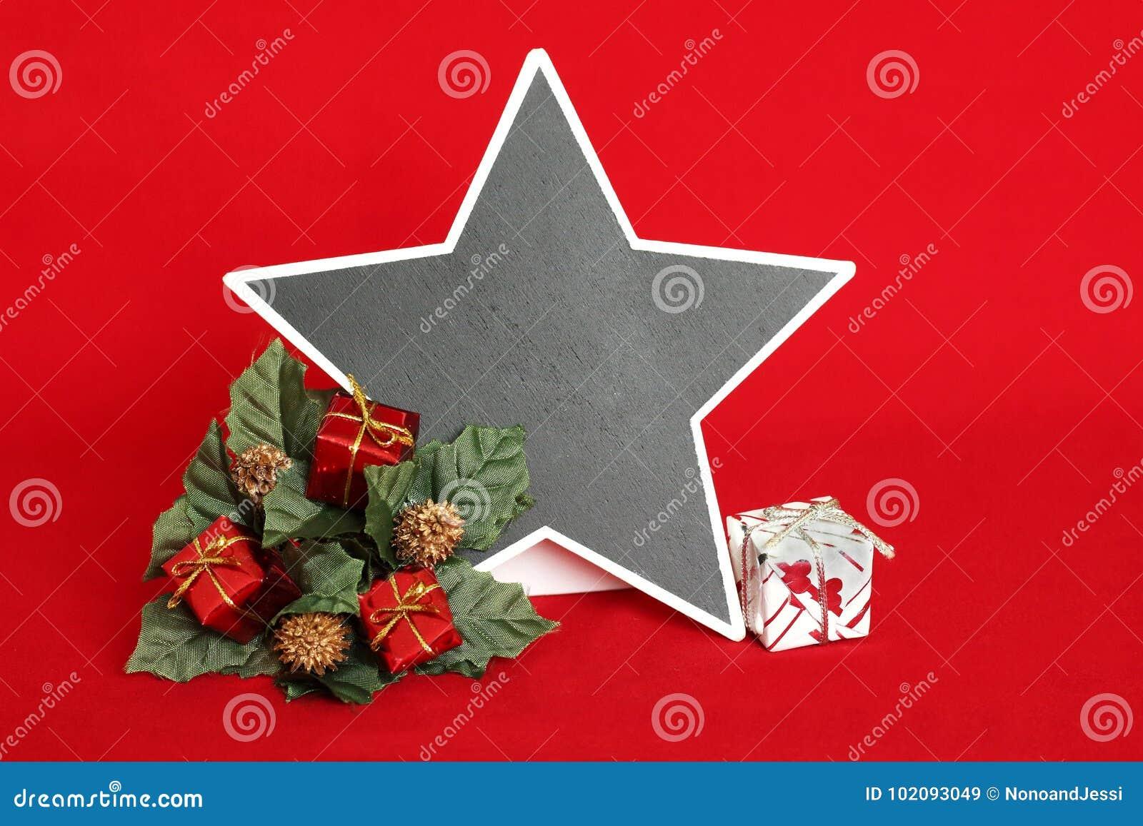 Esvazie a ardósia sob a forma de uma estrela para escrever uma mensagem em um fundo vermelho com os presentes vermelhos e brancos