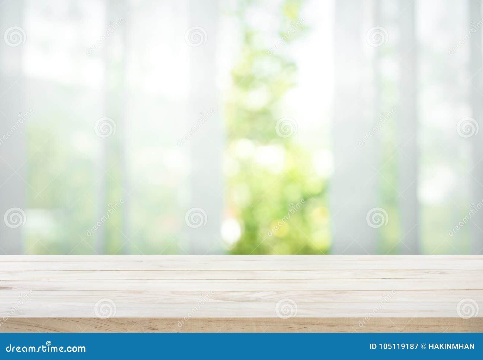 Esvazie do tampo da mesa de madeira no borrão da cortina com verde da opinião da janela do jardim da árvore