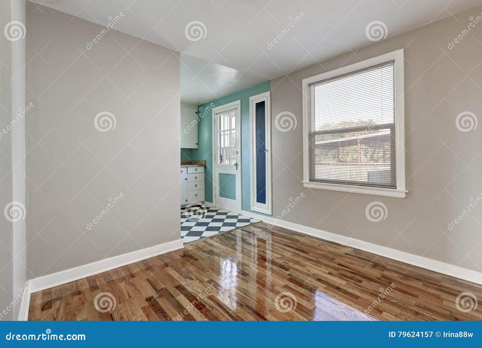 Esvazie a sala bege com o assoalho de folhosa na casa vazia velha